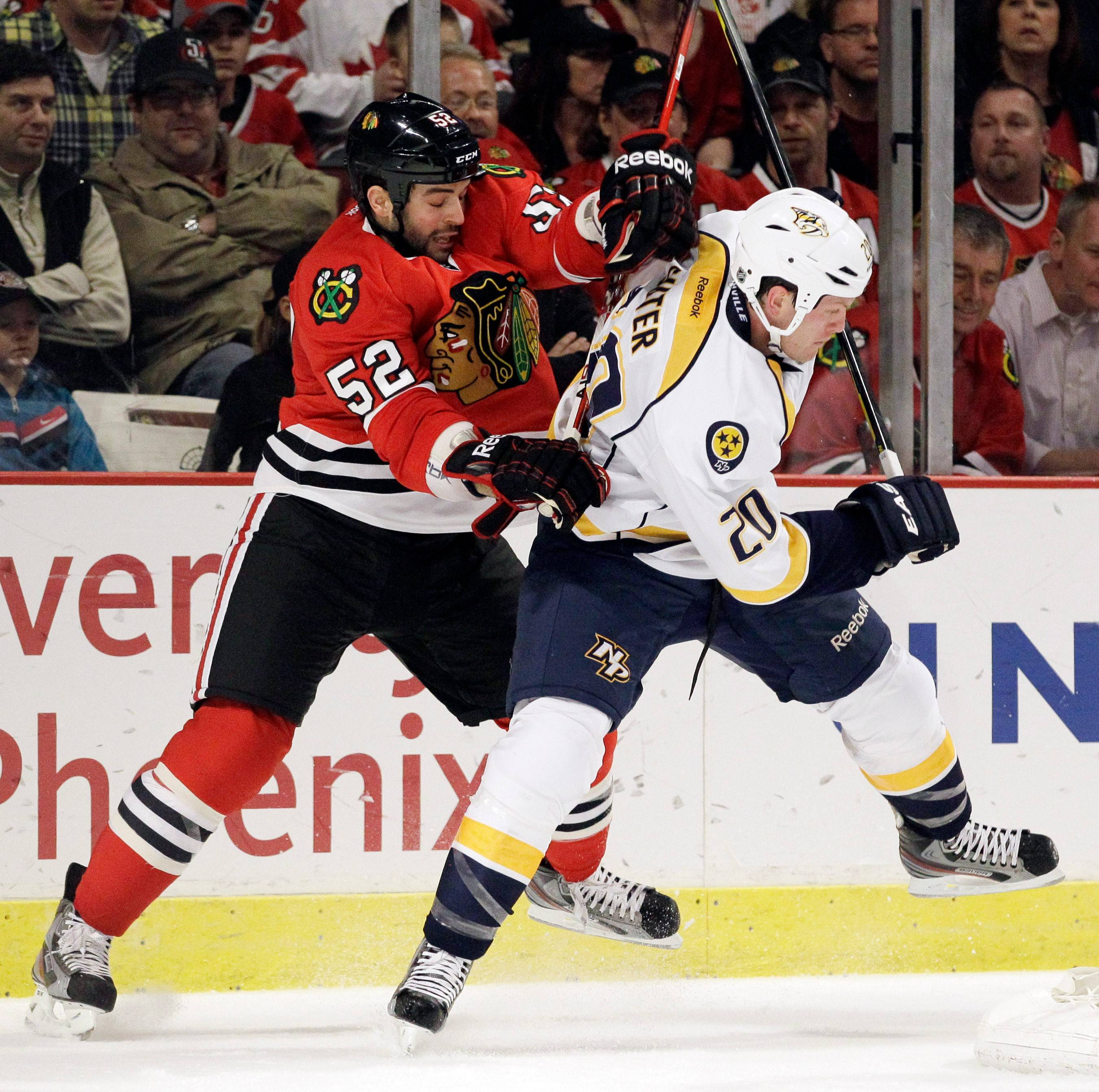 Blackhawks forward Brandon Bollig is checked by the Nashville Predators' Ryan Suter last season. The Blackhawks and Bollig agreed to a three-year contract extension Monday.