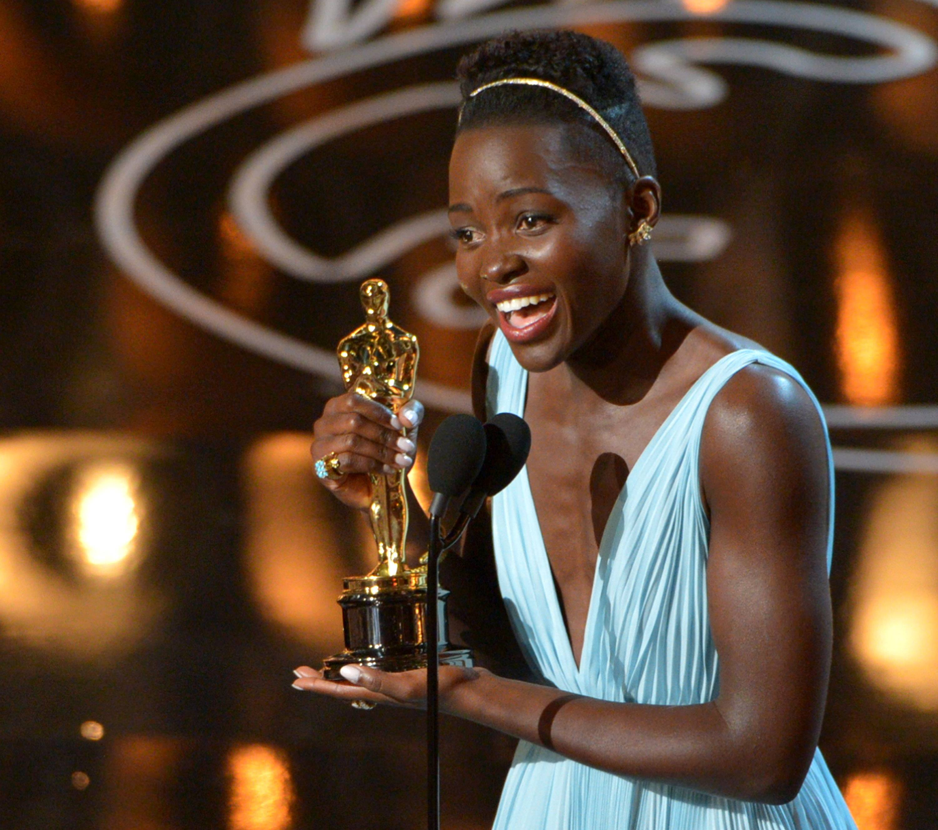 "Lupita Nyong'o accepts the award for best actress in a supporting role for ""12 Years a Slave"" during the Oscars."