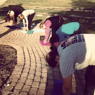 Assurance employees practice sun salutations during an outdoor yoga class in Schaumburg.