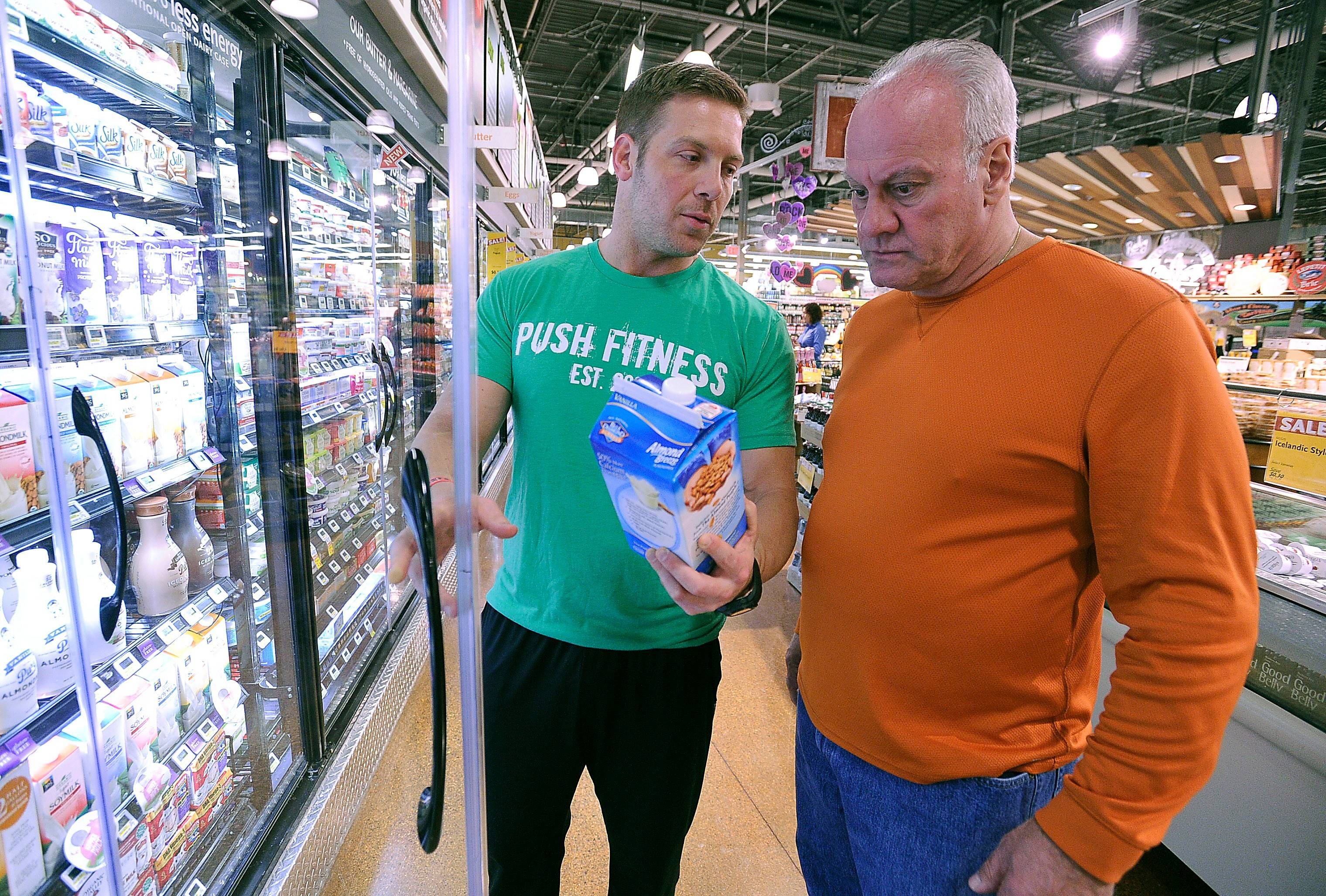 Trainer Brodie Medlock discusses healthy diet choices with Fittest Loser Chris Kalamatas at Whole Foods Market in Schaumburg.