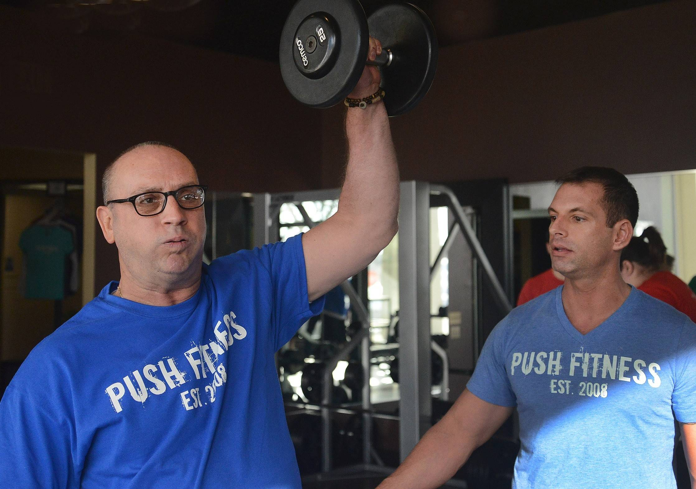 Contestant Tim Lange, left, works out with his trainer, Steve Amsden.