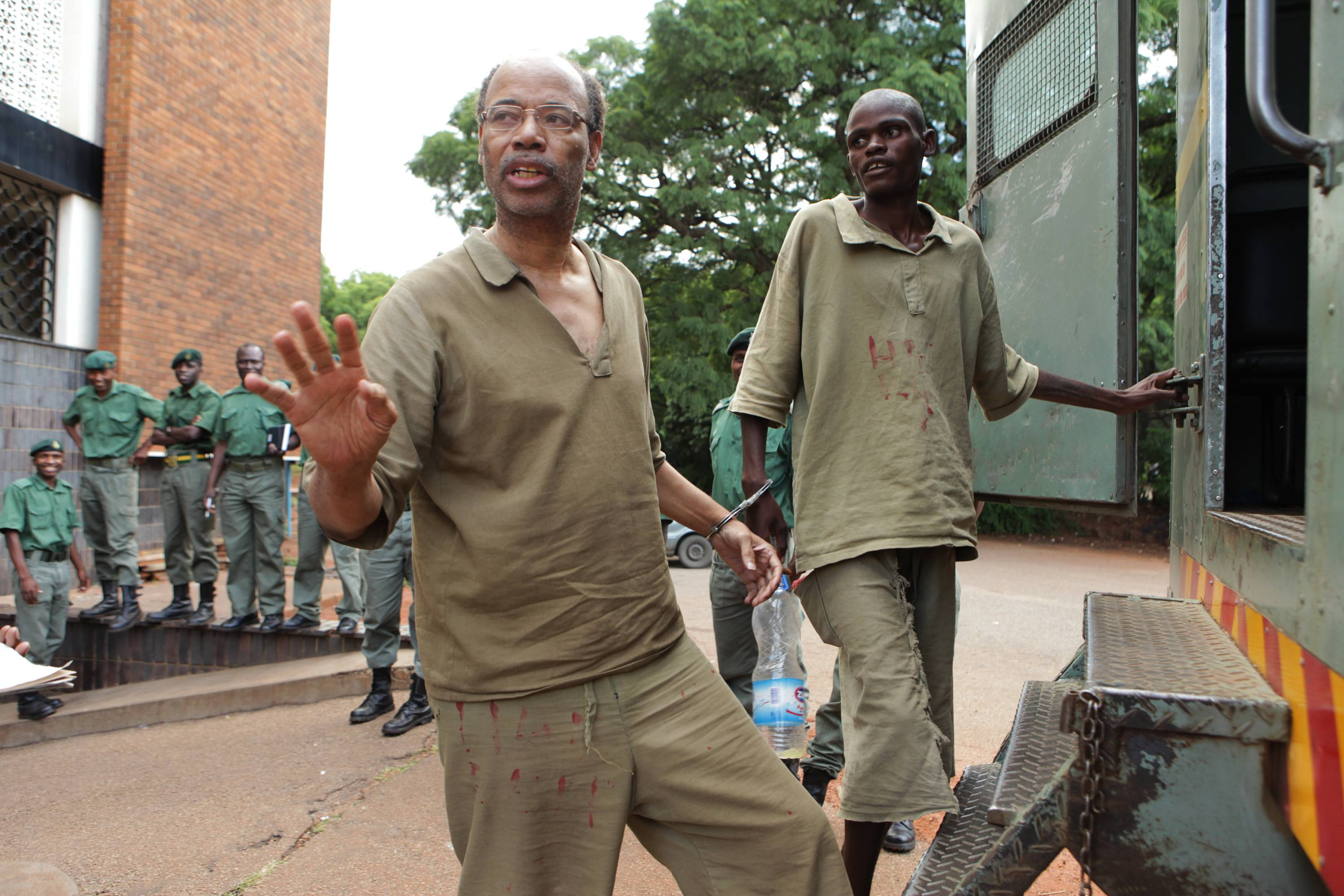 Former Congressman Mel Reynolds, center left, prepares to enter a prison truck while handcuffed after a court appearance Feb. 20 in Harare, Zimbabwe. Since deported, Reynolds now says he's in hiding.
