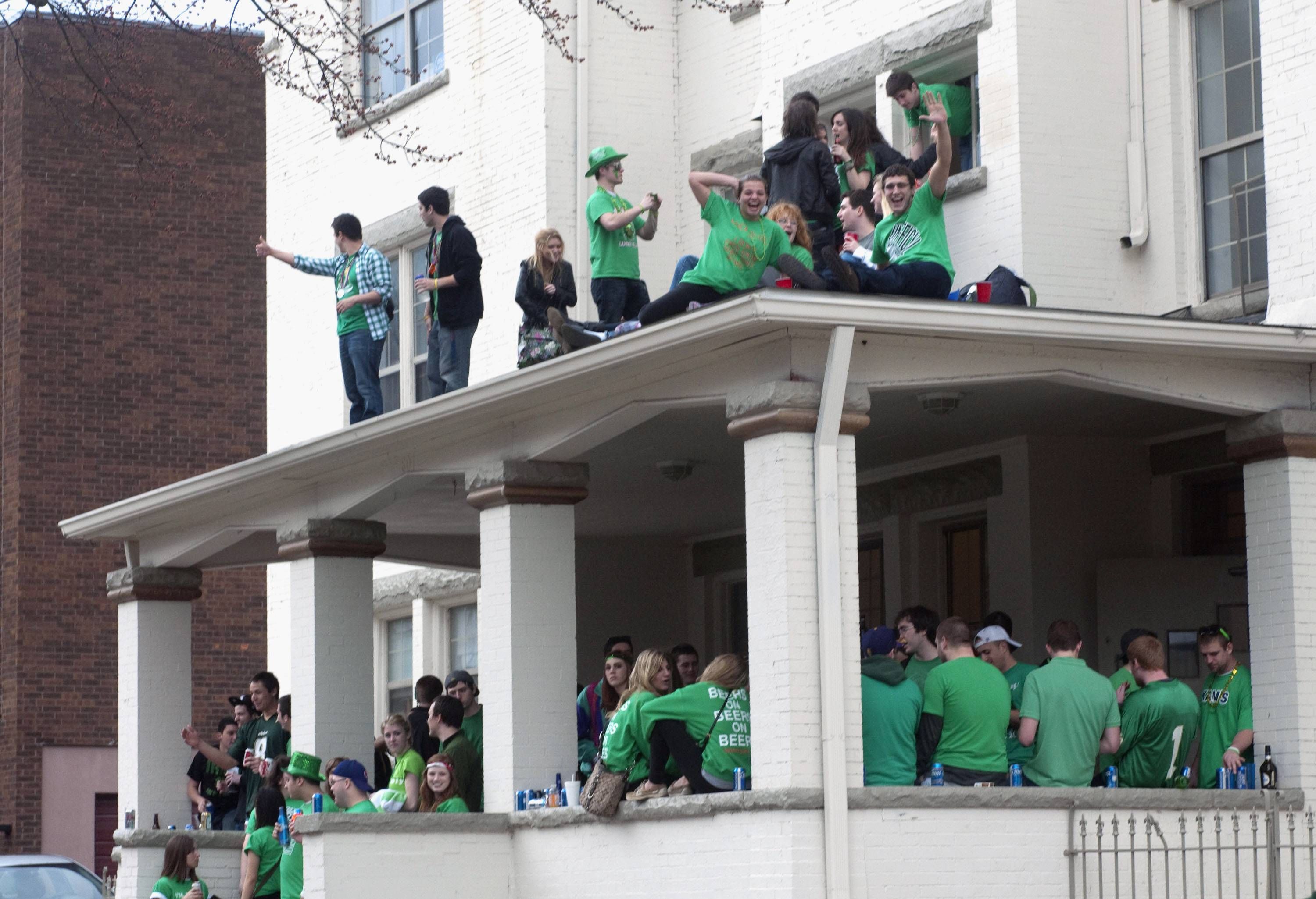 "Students at the University of Illinois gather at a house on campus during the ""Unofficial St. Patrick's Day"" celebration in Champaign. Champaign police say they're gearing up for this year's festivities Friday that are expected to draw thousands of students for a day of drinking."