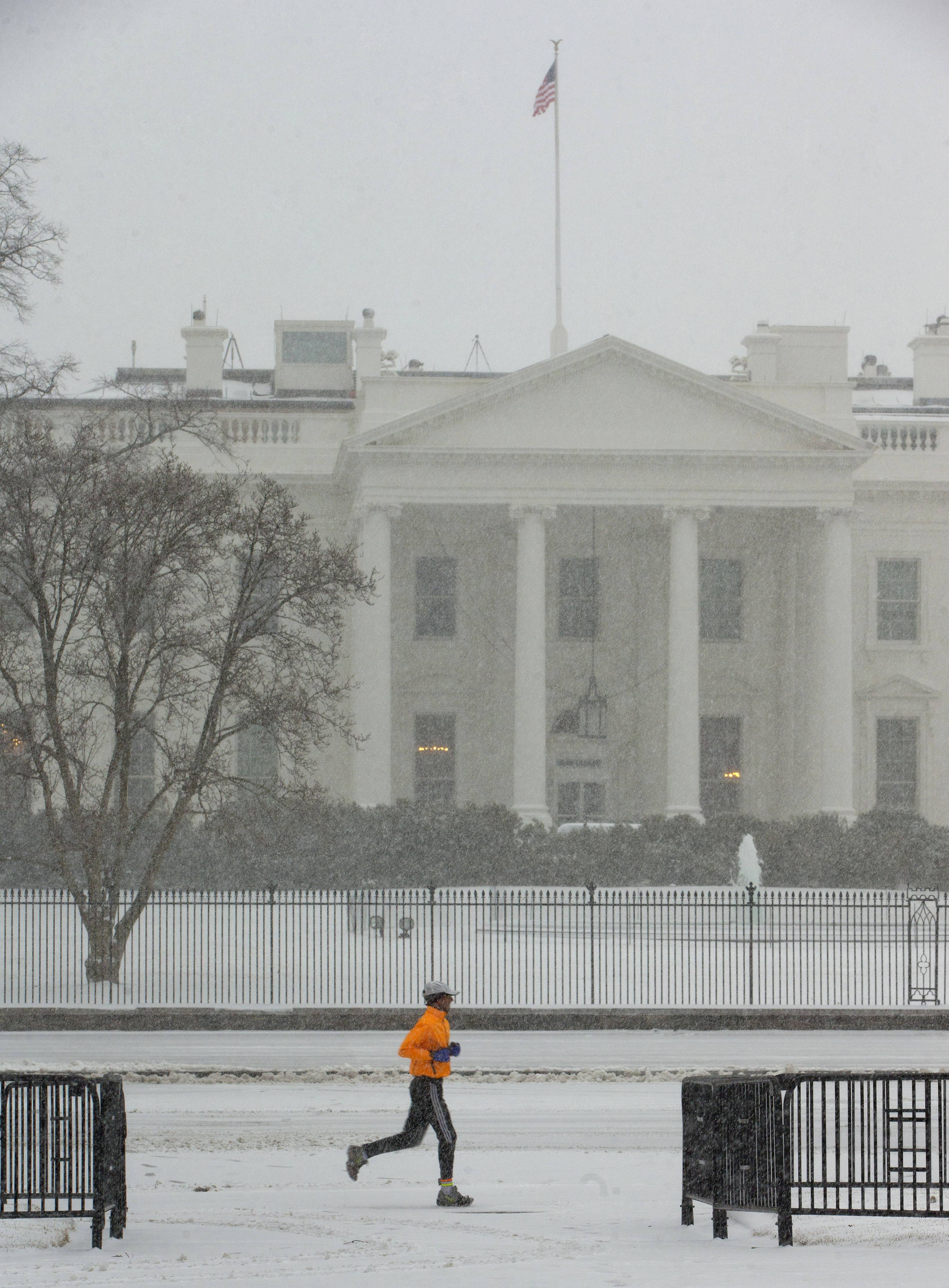 A jogger is seen Monday in Lafayette Park in front of the White House in Washington. The National Weather Service has issued a Winter Storm Warning for the greater Washington Metropolitan region, prompting area schools and the federal government to close for the wintry weather.
