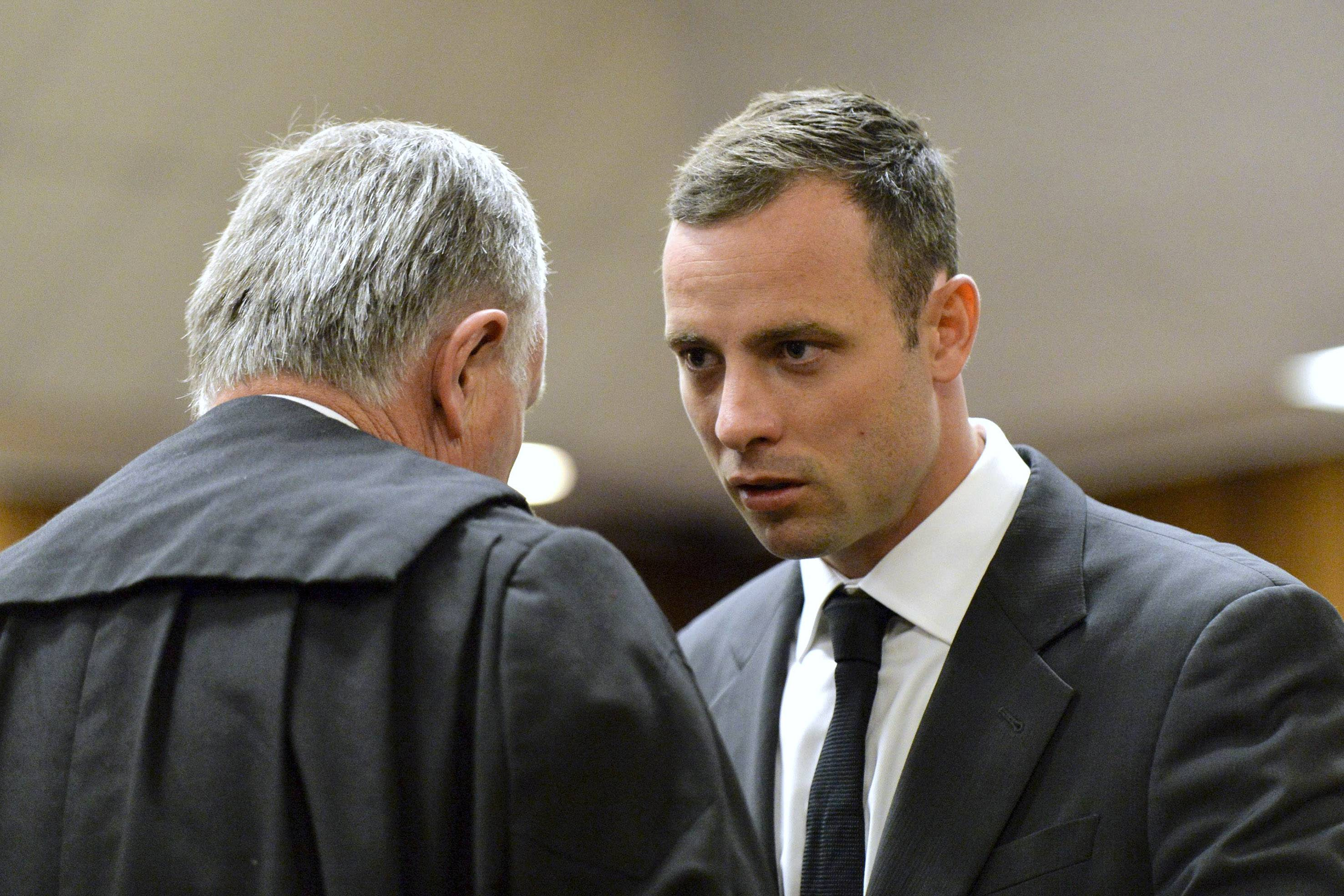 Oscar Pistorius, right, speaks with his lawyer Barry Roux at the start of his trial in Pretoria, South Africa, Monday. Pistorius is charged with murder with premeditation in the shooting death of girlfriend Reeva Steenkamp in the pre-dawn hours of Valentine's Day 2013.