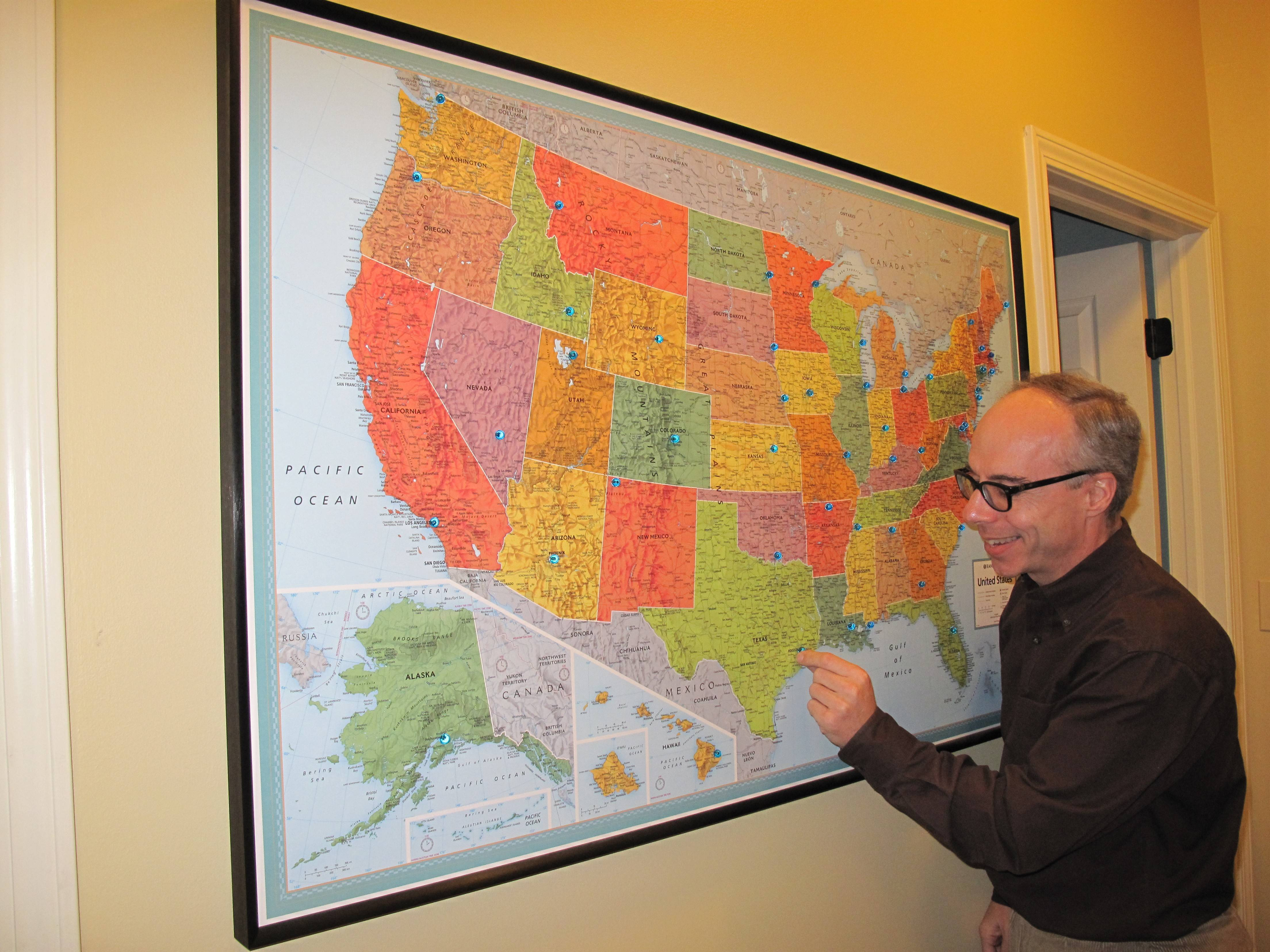 Tom Minichiello of Naperville places a push pin atop Houston, on the map he has used to trace his journey to complete a marathon in less than four hours in all 50 states. He reached his goal Jan. 19 in Houston.