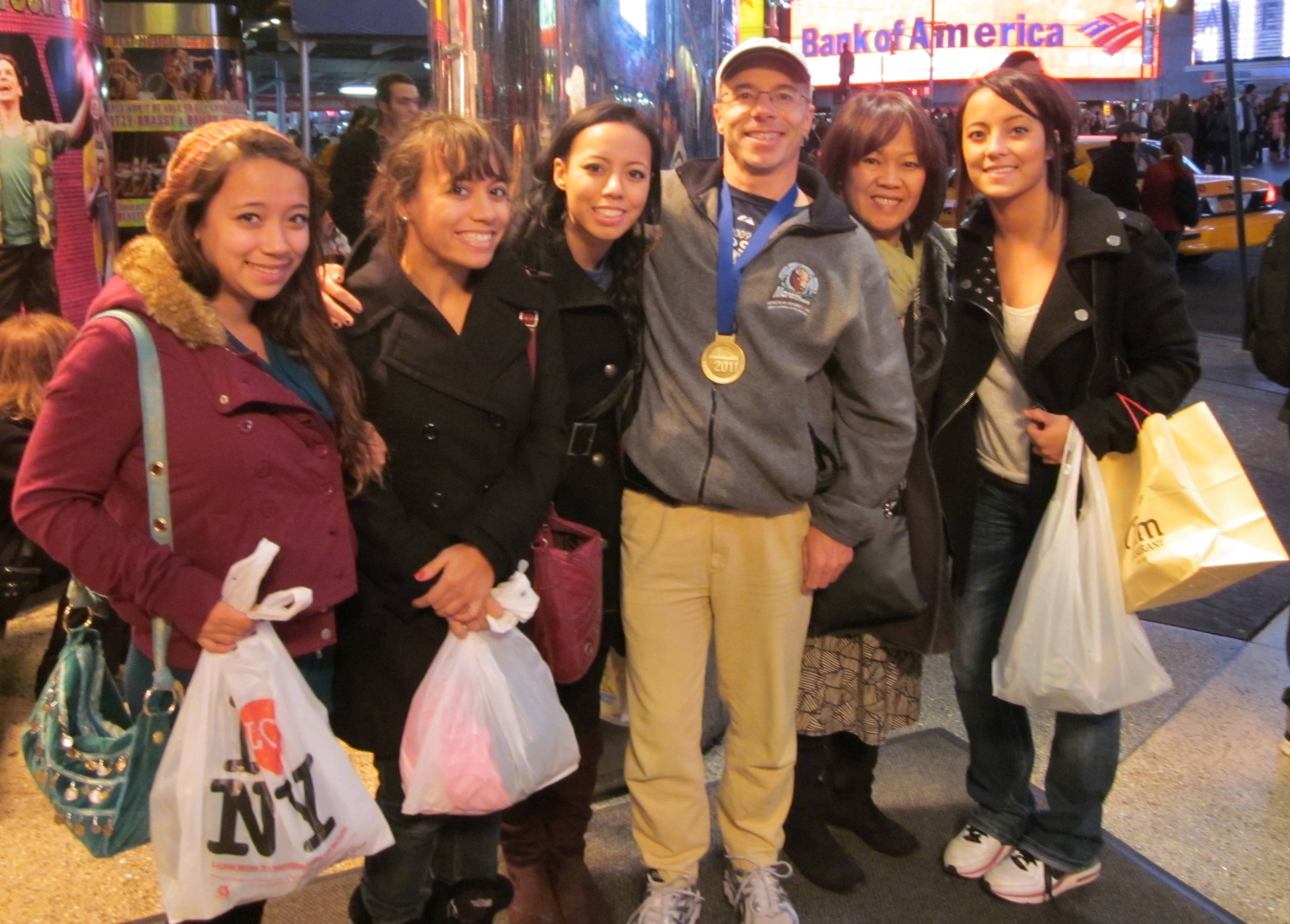 Tom Minichiello celebrates his completion of the New York City Marathon in November 2011 with his family at Times Square. Seen with him are daughters Michelle, now 17, Susan, now 25, Amy, now 24, his wife Suphan and daughter Leslie, now 22.