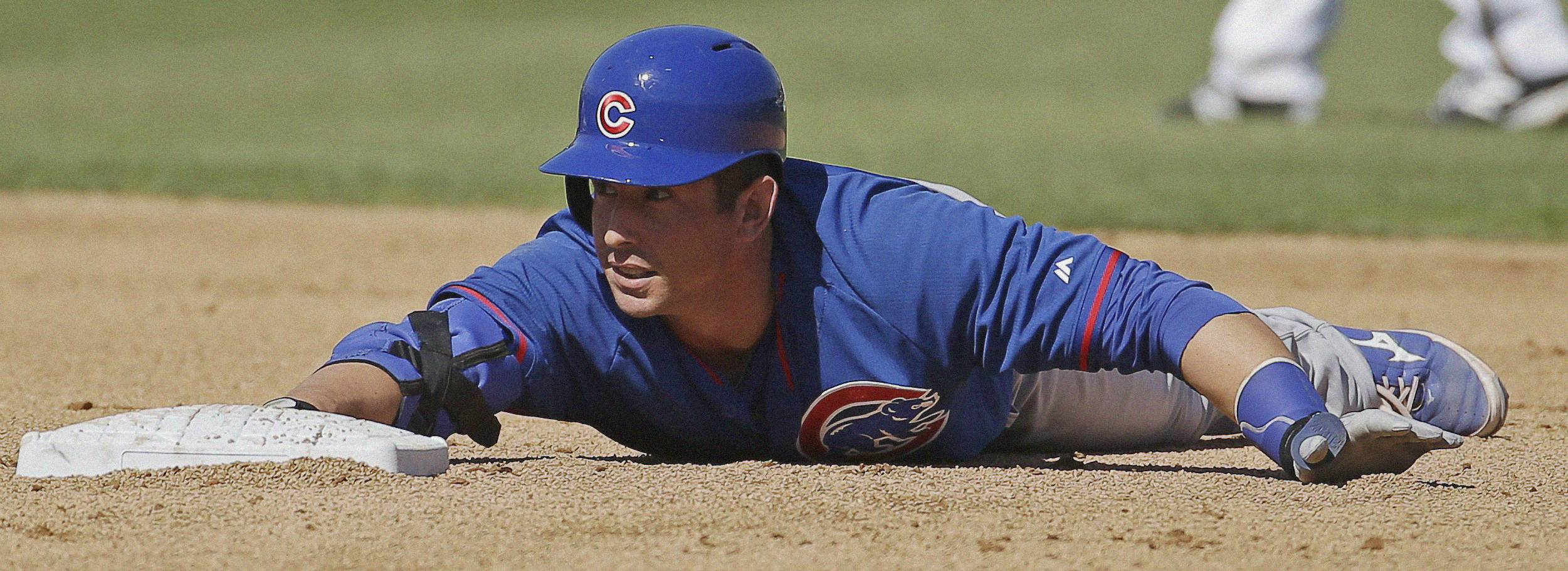 The Cubs' John Baker slides into second for a double during the fourth inning of Monday's spring training game against the Milwaukee Brewers.