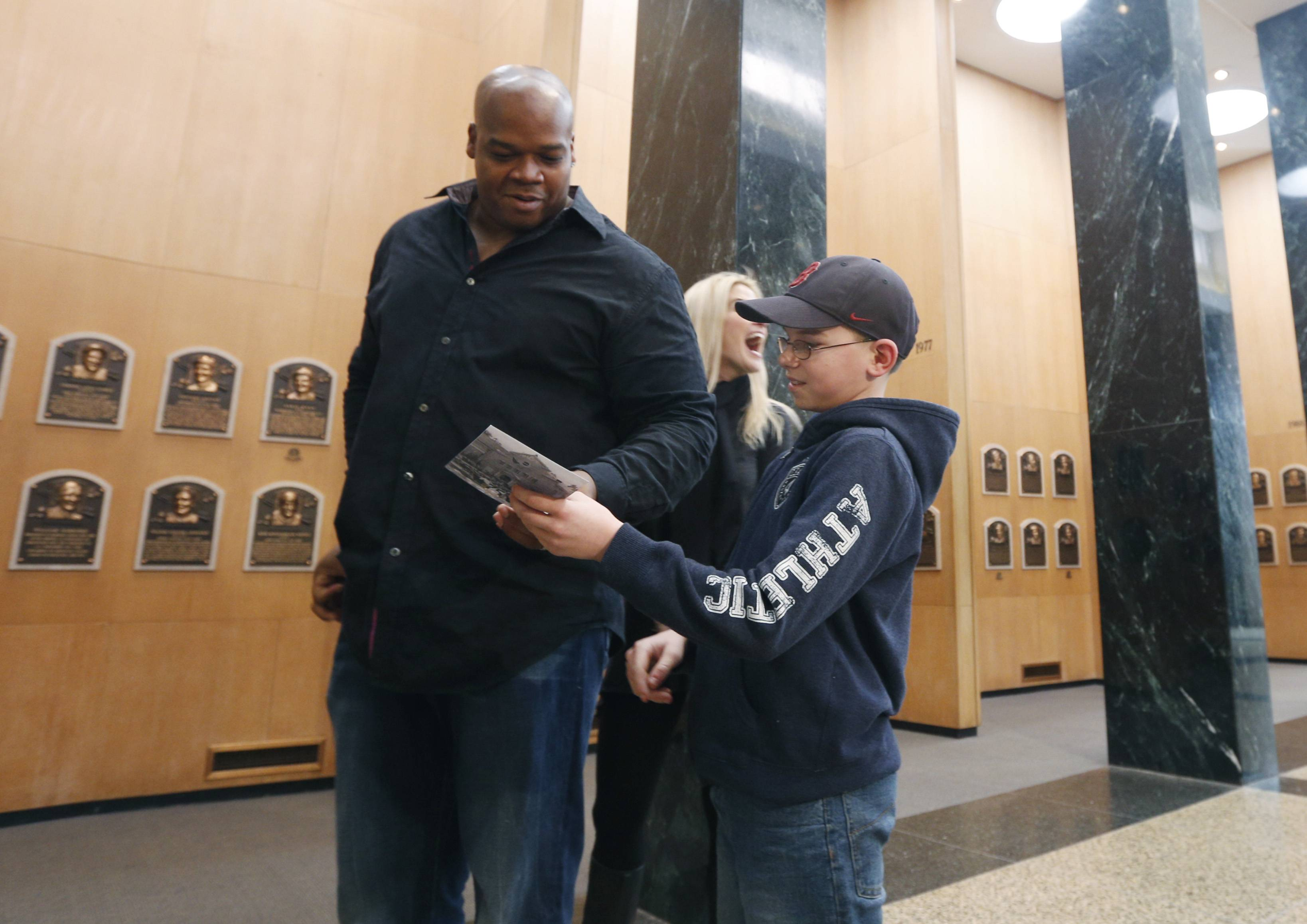 Frank Thomas signs an autograph for Joseph Grande of Wheatfield, N.Y., on Monday during his orientation visit at the Baseball Hall of Fame.