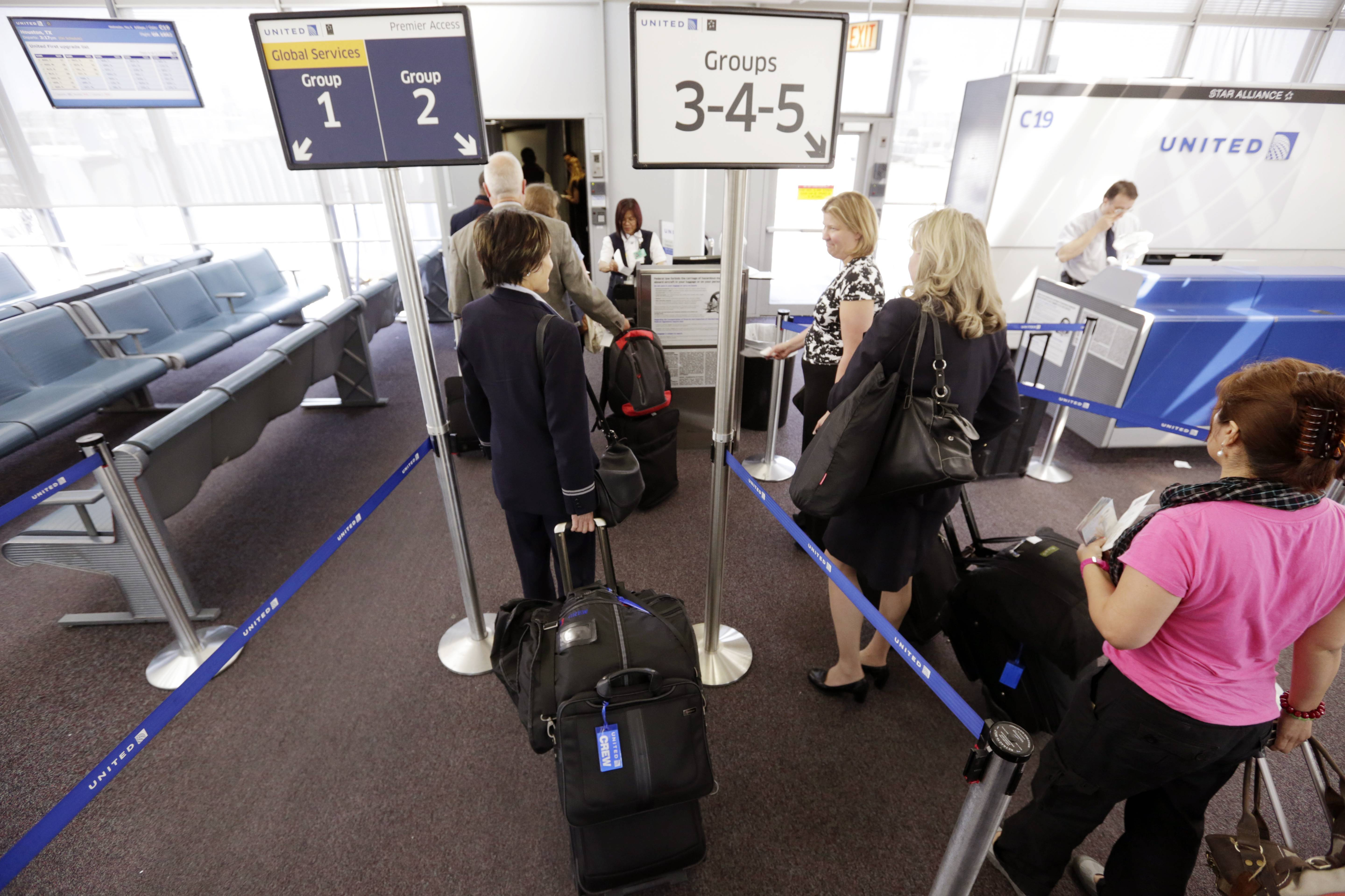 Passengers wait at a United Airlines gate to board a flight in separate numbered lanes at O'Hare International Airport in Chicago. In February, United Airlines installed new bag sizers at airports and emailed its frequent fliers, reminding them of their carry-on size rules.