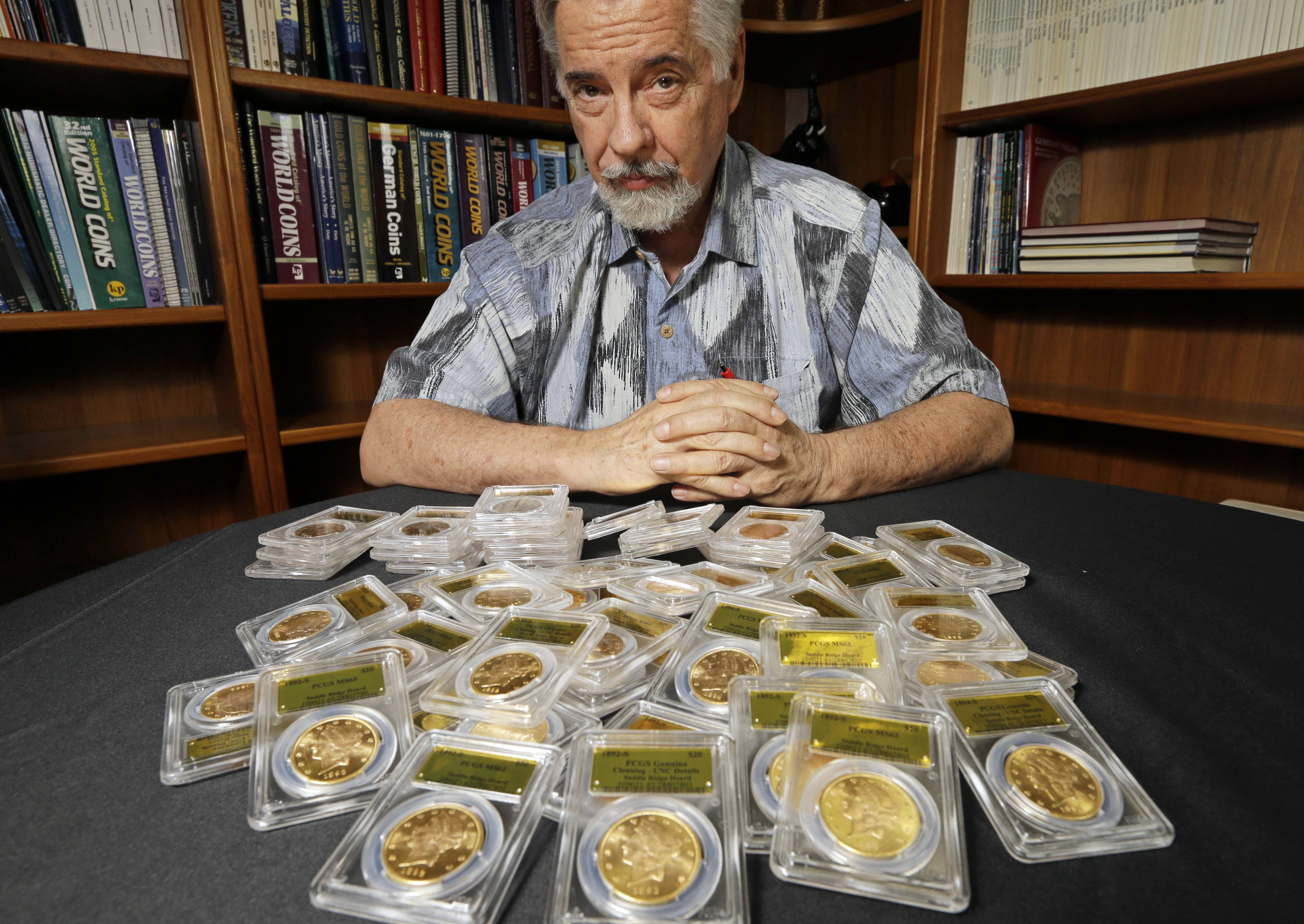 David Hall, co-founder of Professional Coin Grading Service, poses with some of 1,427 Gold-Rush era U.S. gold coins, at his office in Santa Ana, Calif. A California couple out walking their dog on their property stumbled across the modern-day bonanza.