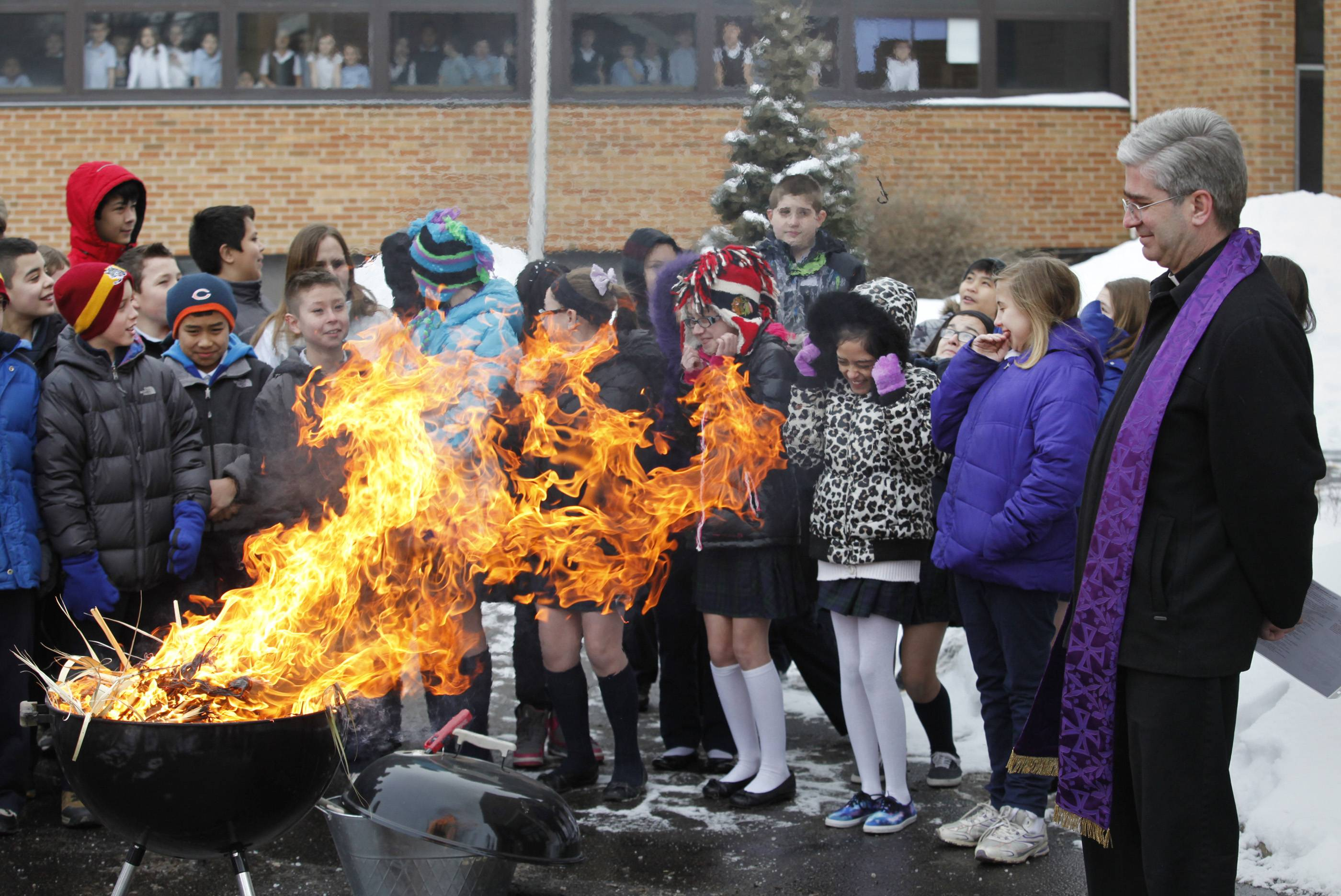 Students from St. Laurence Catholic School in Elgin have varying reactions to the flames and smoke as the Rev. Andrew Mulcahey burns palms Tuesday in preparation for Ash Wednesday.