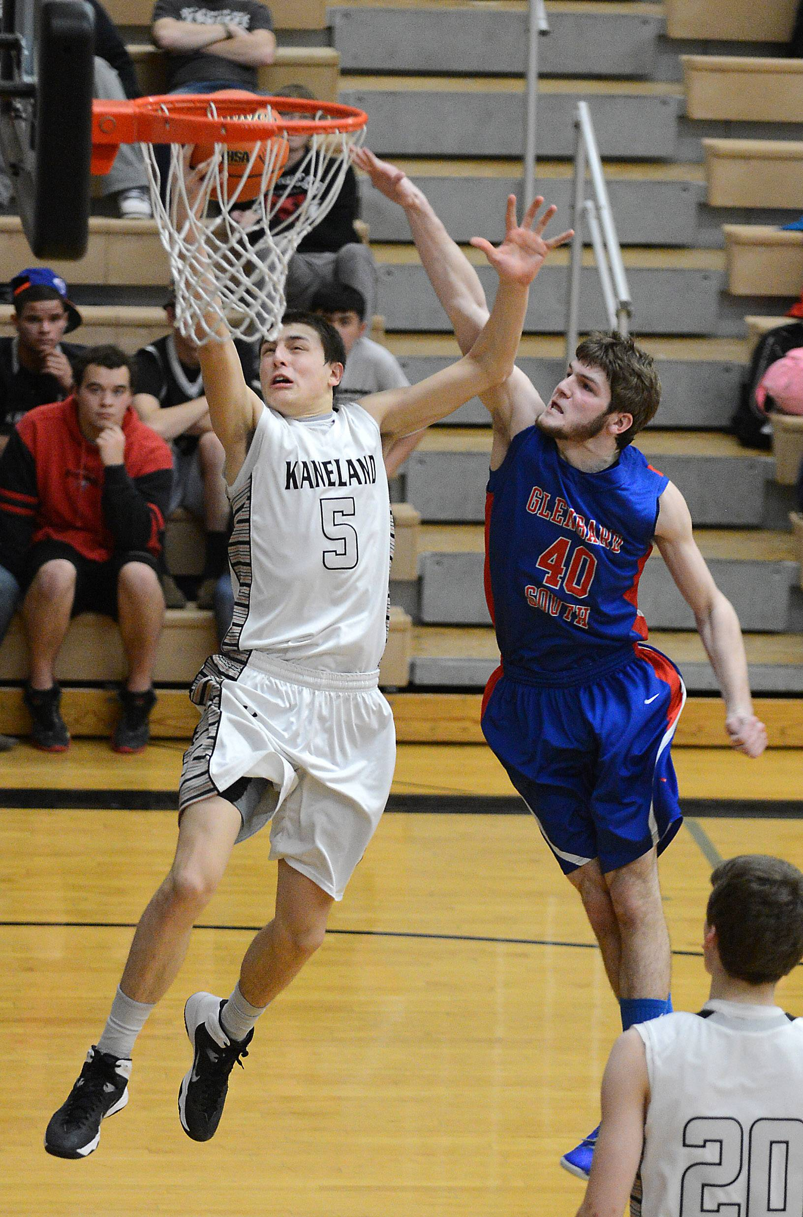 Kaneland's John Pruett (5) scores on a breakaway while fending off Glenbard South's John Marks (40) during Tuesday's regional action in Kaneland.