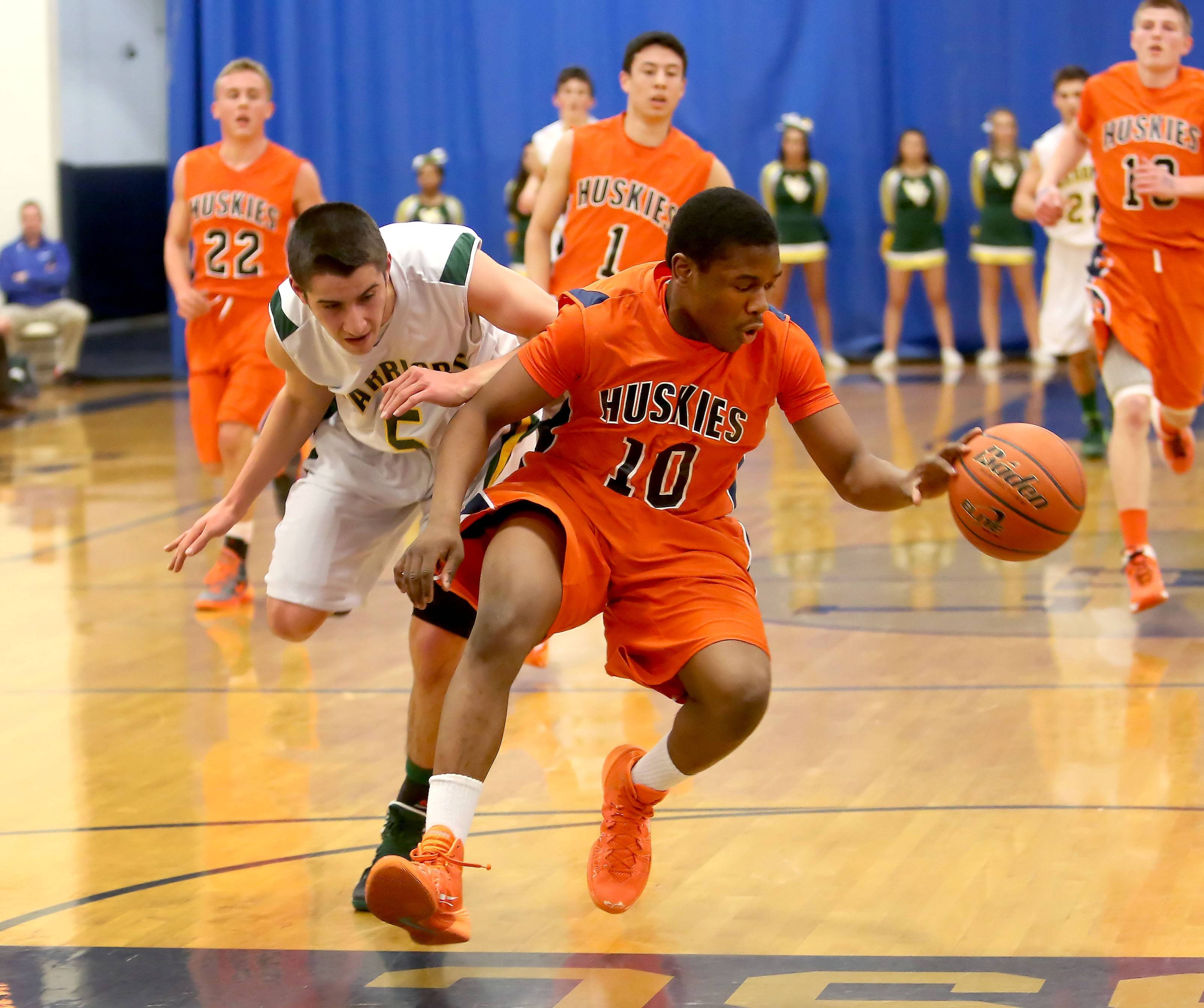 Naperville North's Jelani McClain Jr., right, grabs a loose ball in midcourt from Nick Karkazis, left, of Waubonsie Valley.