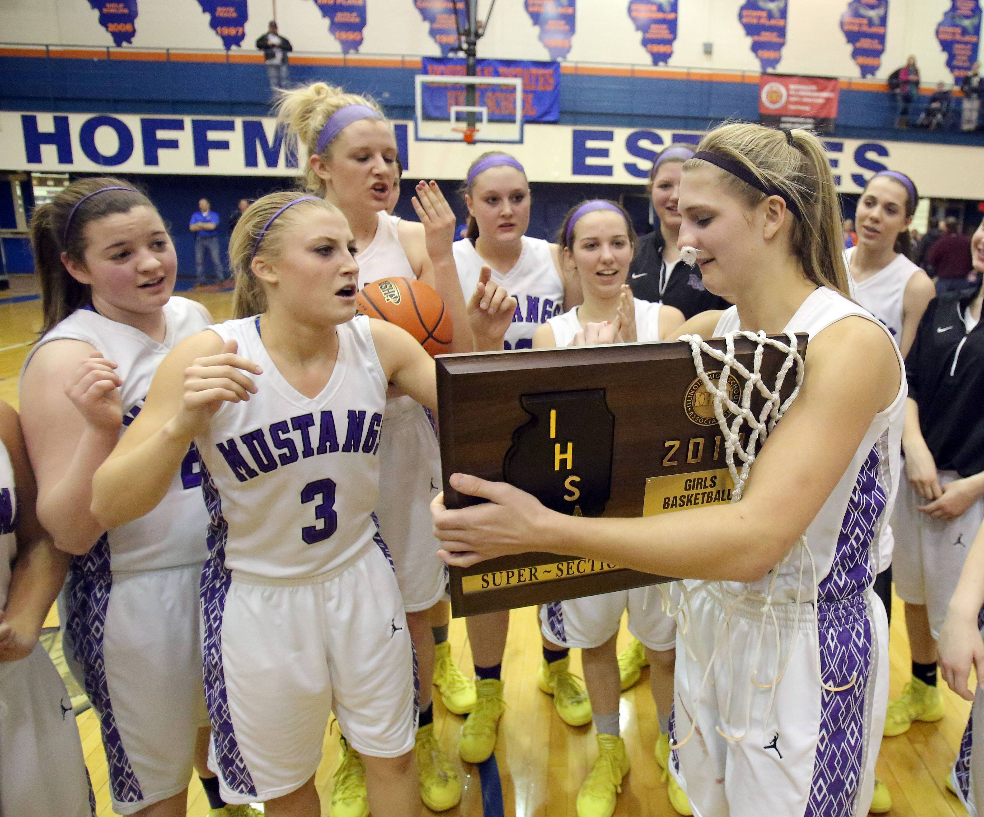Rolling Meadows players gather around Alexis Glasgow as she receives the supersectional trophy after the Mustangs topped New Trier 60-43 in the Class 4A supersectional game at Hoffman Estates on Monday. Glasgow suffered a broken nose in the game but has been cleared to play in Friday's state semifinal against Geneva.