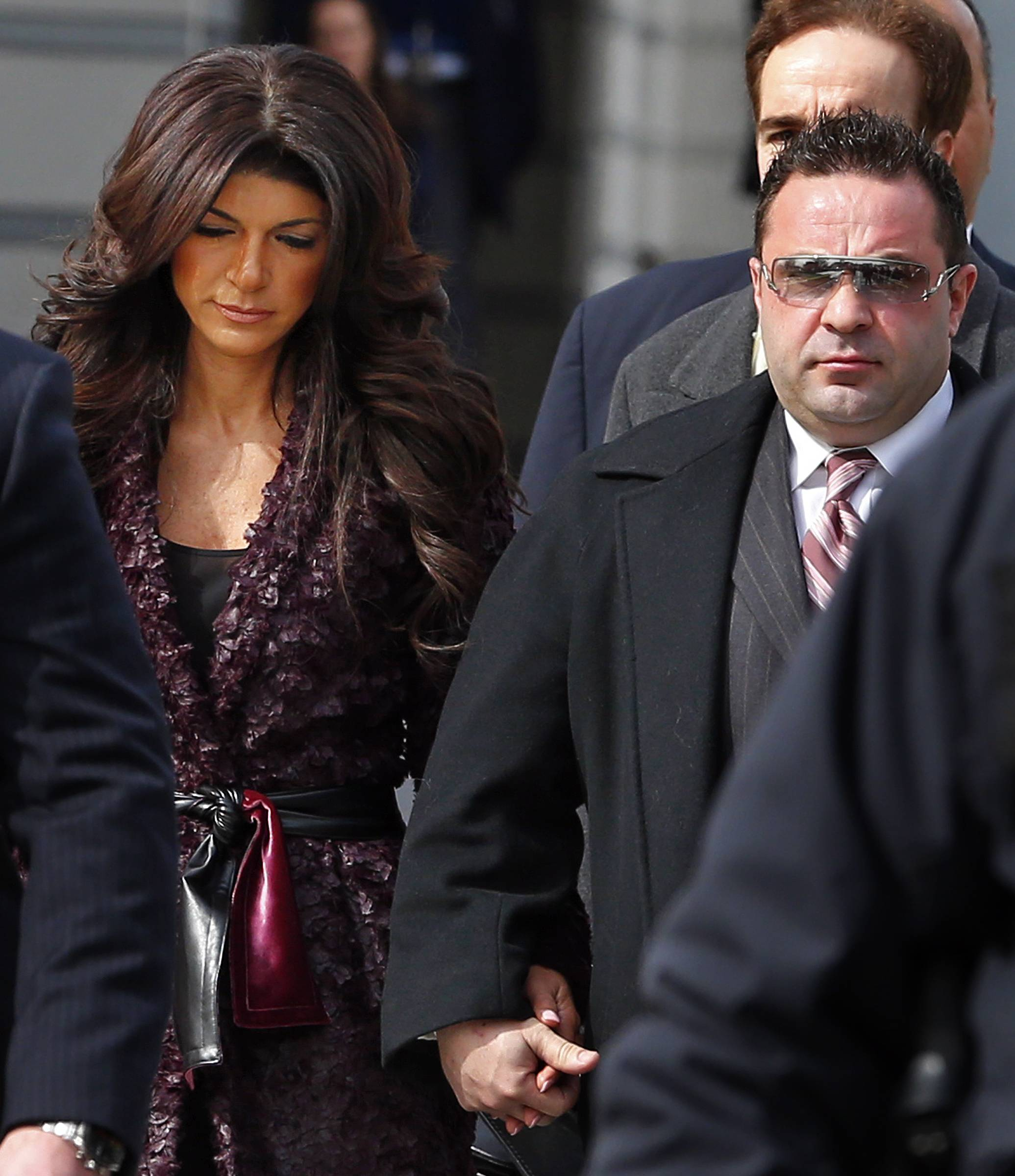 "Teresa and Joe Giudice, from ""The Real Housewives of New Jersey,"" leave federal court in Newark, N.J., on Tuesday. They each pleaded guilty to several counts including bankruptcy fraud, conspiracy to commit mail fraud and wire fraud, and failing to pay taxes."