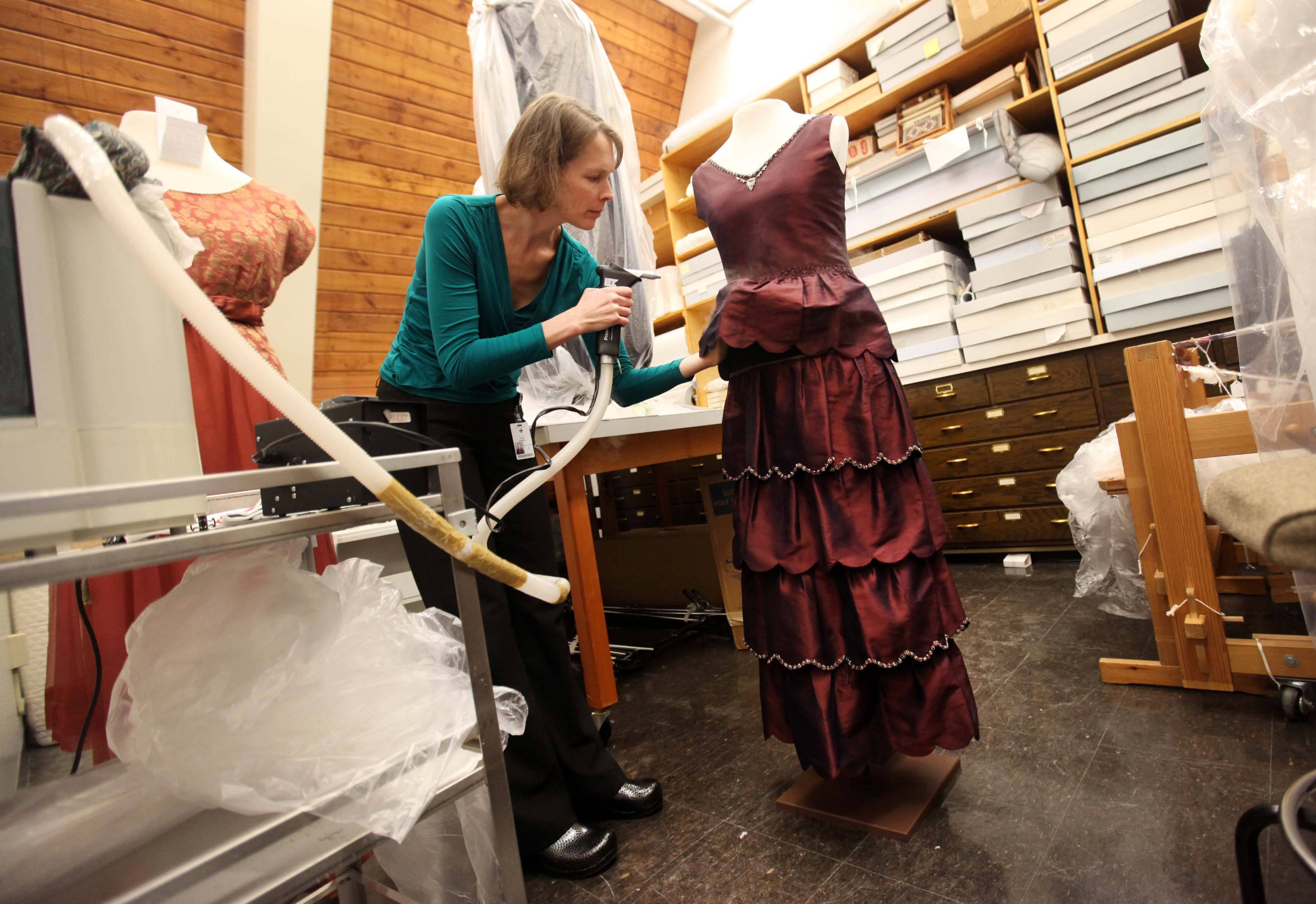 "Kate Sahmel, a textile conservator, steams the engagement dress of character Mary worn in the British television drama ""Downton Abbey"" during preparations for an exhibit at the Winterthur Museum in Wilmington, Del."