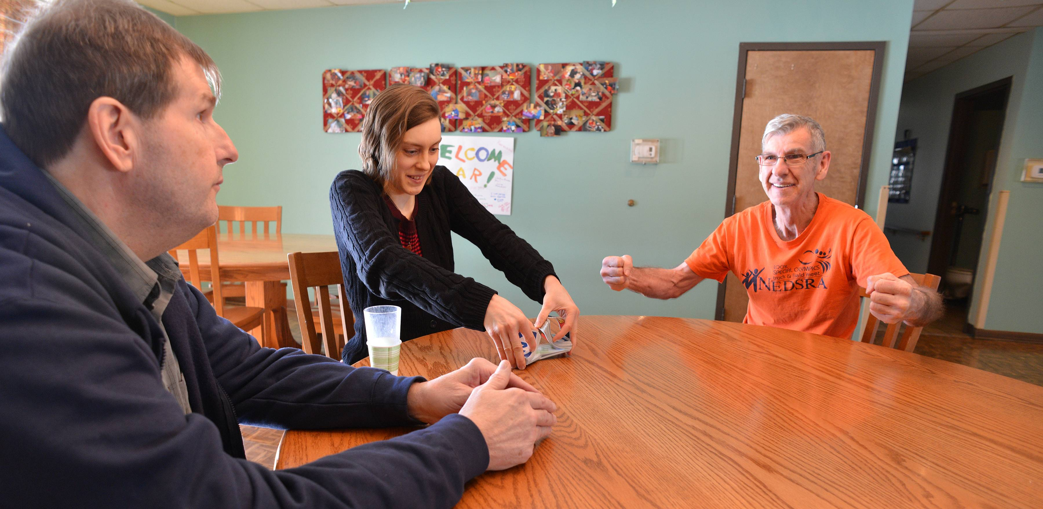 Deicke Home volunteer Tiffany Brownlie, center, plays cards with residents Jim Bosh and Eddie Doutlick. Officials at the home, which serves high-functioning adults with disabilities, originally feared it would have to close at the end of March. Now, they say, an outpouring of community support will keep it open at least until the end of July.
