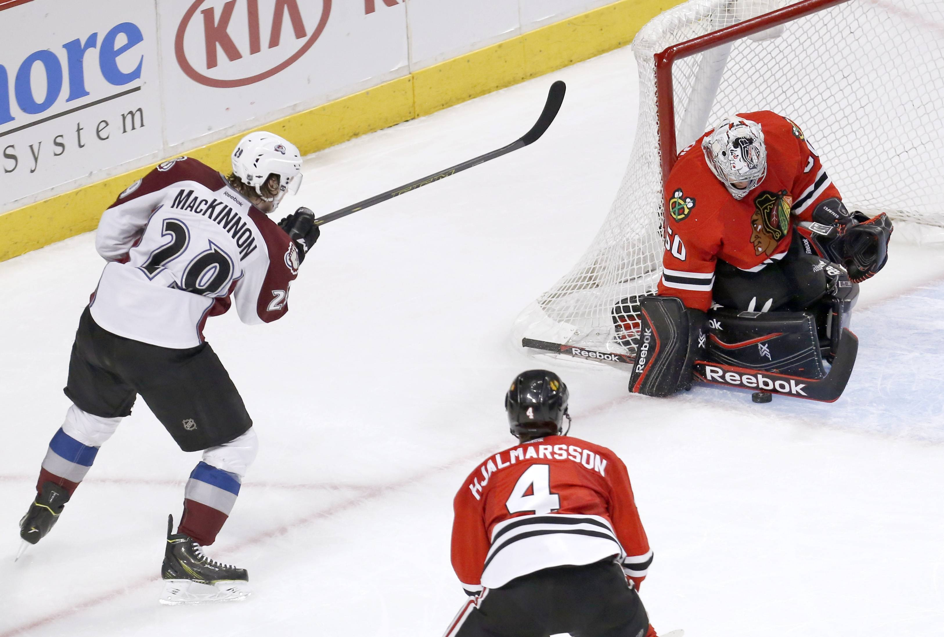Chicago Blackhawks goalie Corey Crawford (50) makes a save on a shot by Colorado Avalanche center Nathan MacKinnon (29) as Niklas Hjalmarsson (4) watches during Tuesday night's match at the United Center.
