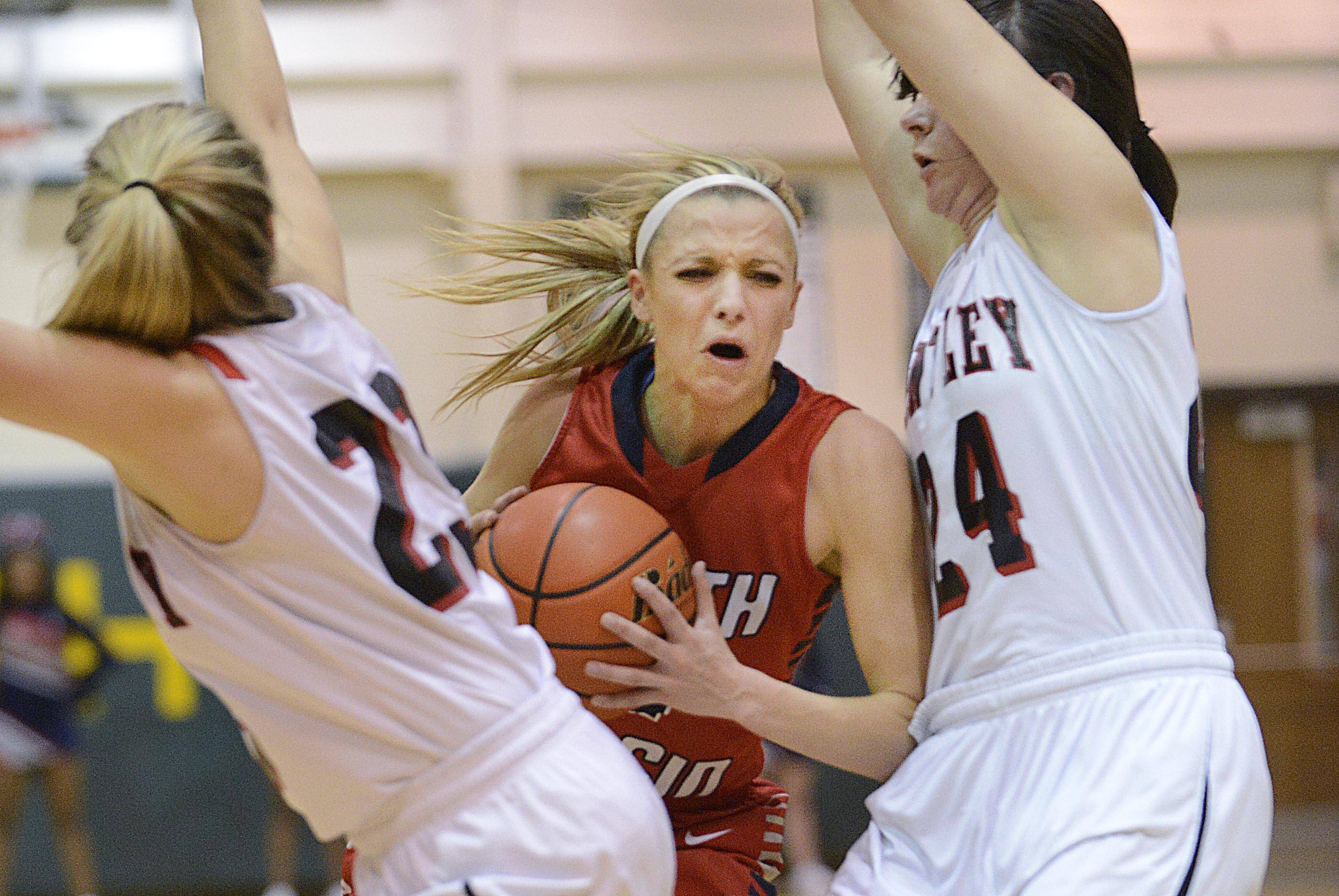 South Elgin's Savanah Uveges pushes past Huntley's Bethany Zornow and Jessica Brock in the Class 4A Crystal Lake South sectional game Tuesday.
