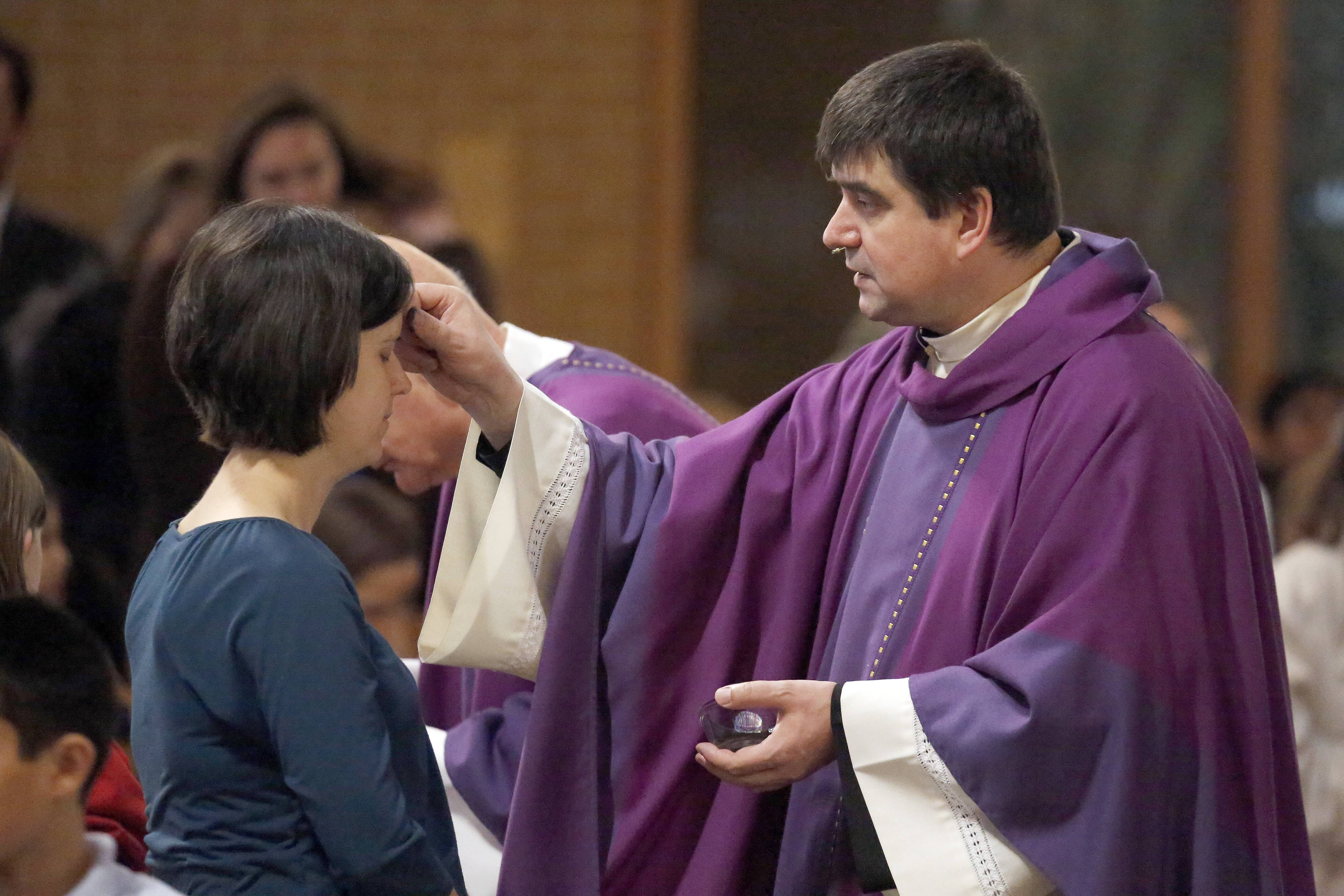 Father Peter Sarnicki, right, puts ashes on St. Margaret Mary Catholic School teacher Rachel Urbaszewski.