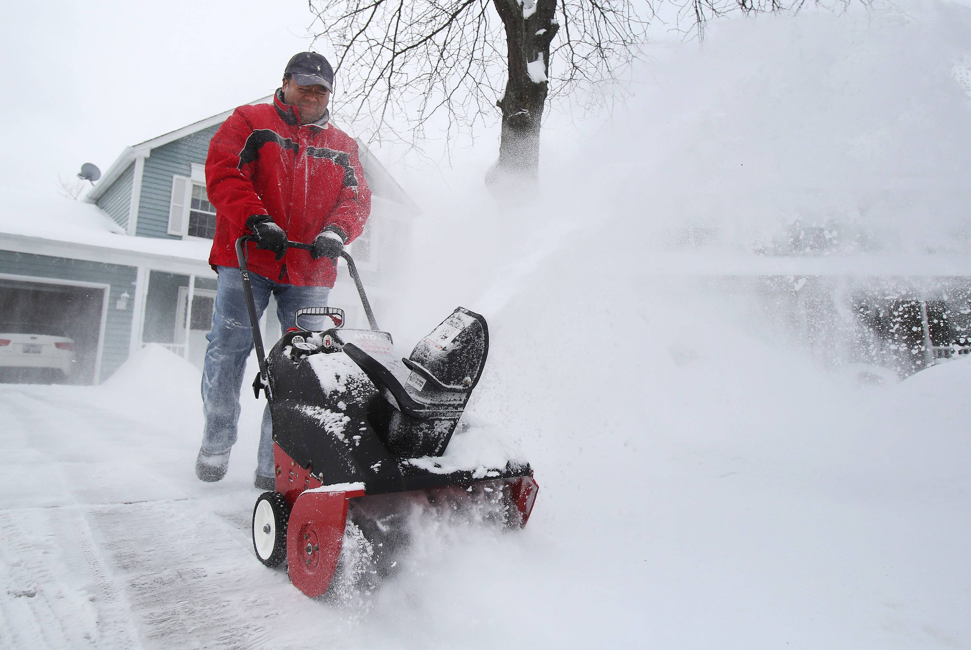 Mundelein resident Jose Ruiz clears his driveway along Bristol Court with a snowblower Wednesday morning after an overnight snowstorm swept through Lake County. A winter weather advisory remains in effect for the suburbs until noon today.