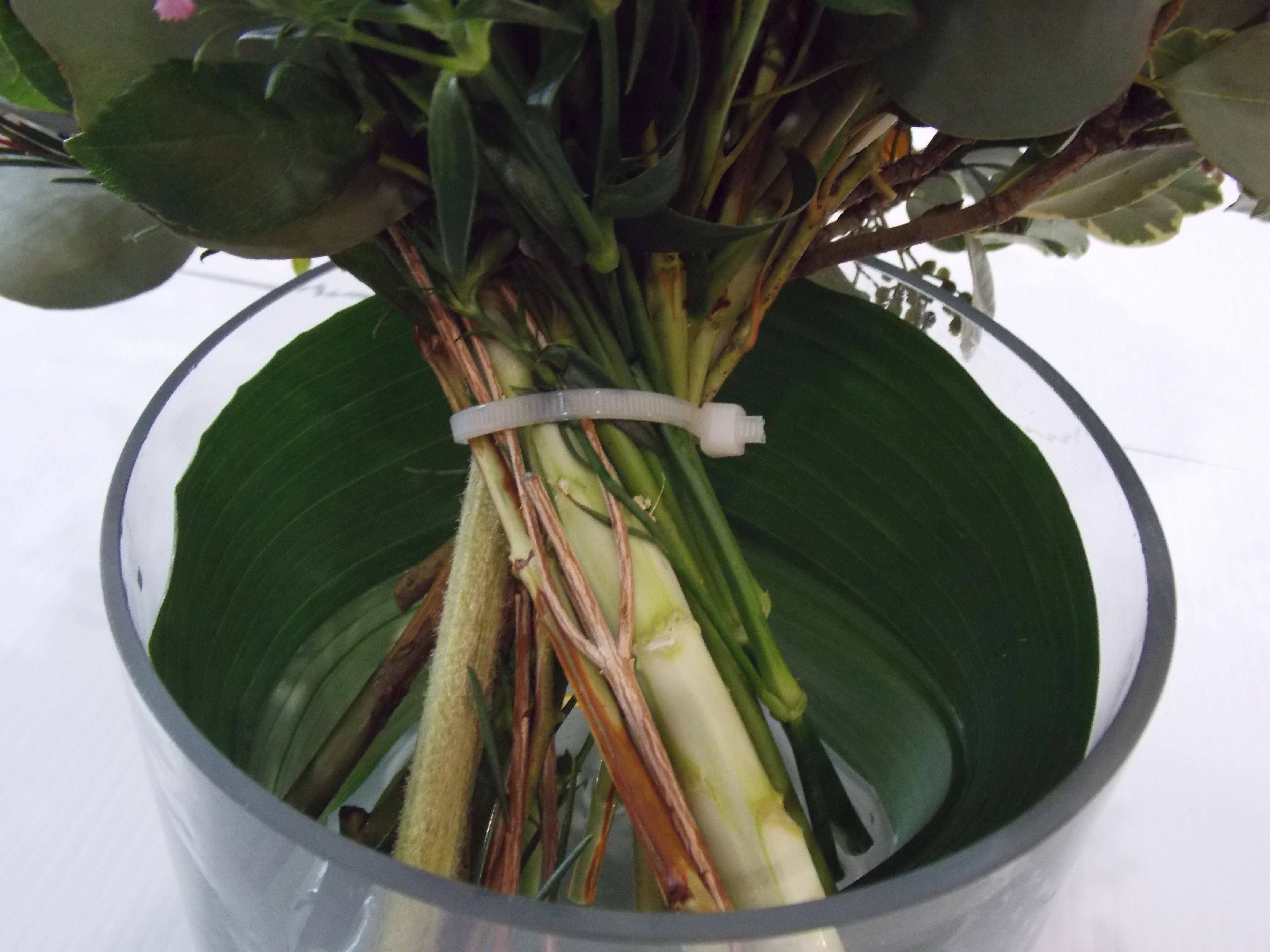 When your vase is too wide to hold the bouquet tightly in place: Use a nylon zip tie, wrapping it around the bouquet's stems and cutting off the tie's excess length. In order to hide the tie, either use ribbon, or try fresh, Aspidistra foliage. The large leafs can be 2-3 inches wide and do well under water. Simply cut the stems off and loop the foliage around the vase.