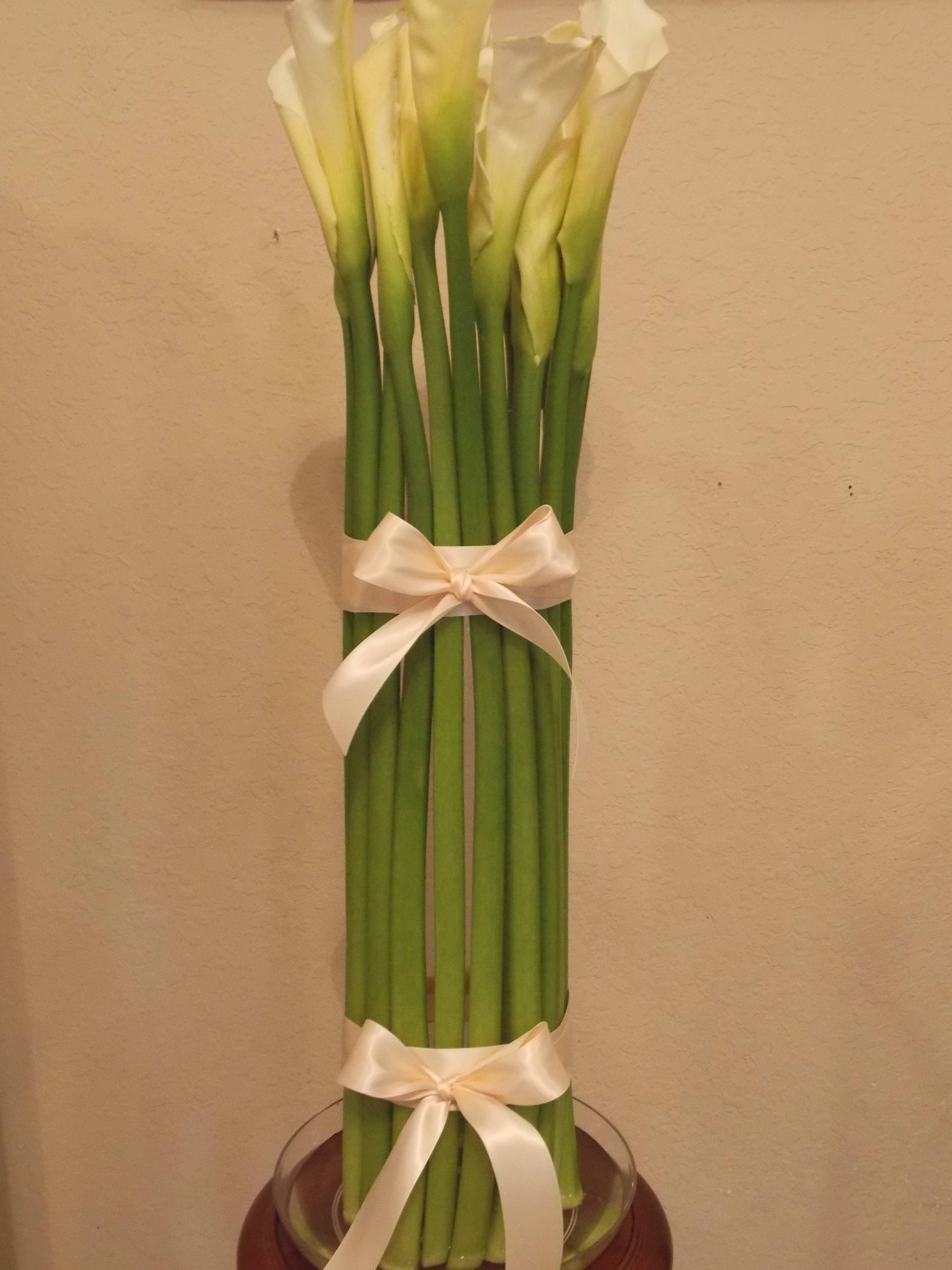 THINK OUTSIDE THE VASE: Put the flowers outside the container and get a cool, columnar design. Using a cylinder-shaped vase, 4 inches wide and 10 inches high, place two rubber bands horizontally around the cylinder. Slide calla lilies between the bands and vase. Put foliage band or ribbon band to conceal the rubber bands. Place vase into a clear dish to keep the calla lilies hydrated.