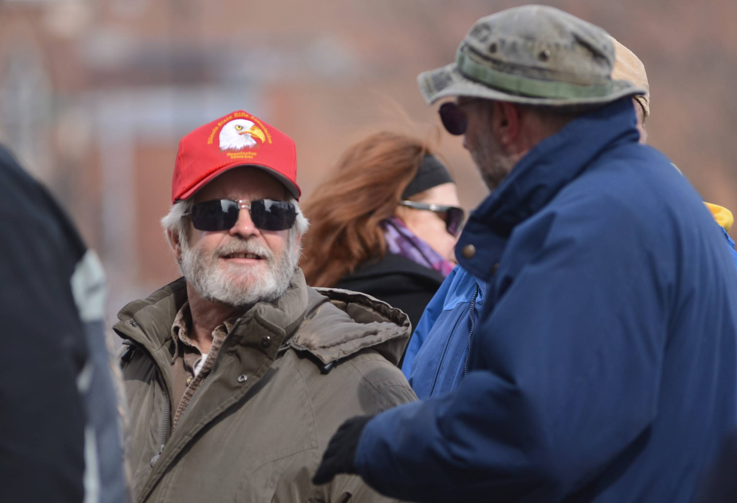 Tom Mishler, 65, left, of Woodstock listens to Mark Gampl, 54, of McHenry as they wait to enter the Illinois Capitol Wednesday.
