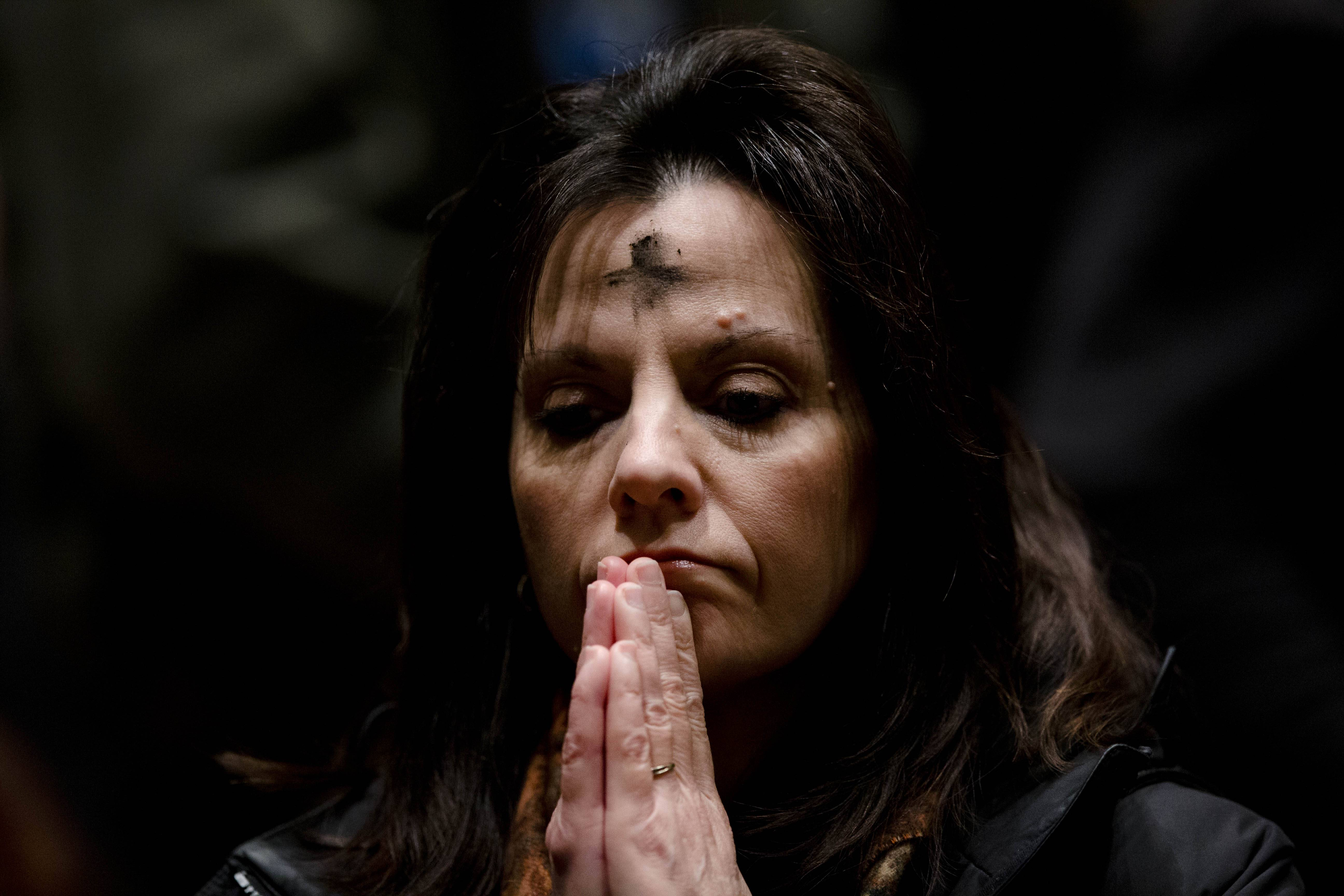 A woman prays as she participates in an Ash Wednesday Mass at the Cathedral Basilica of Saints Peter and Paul in Philadelphia.