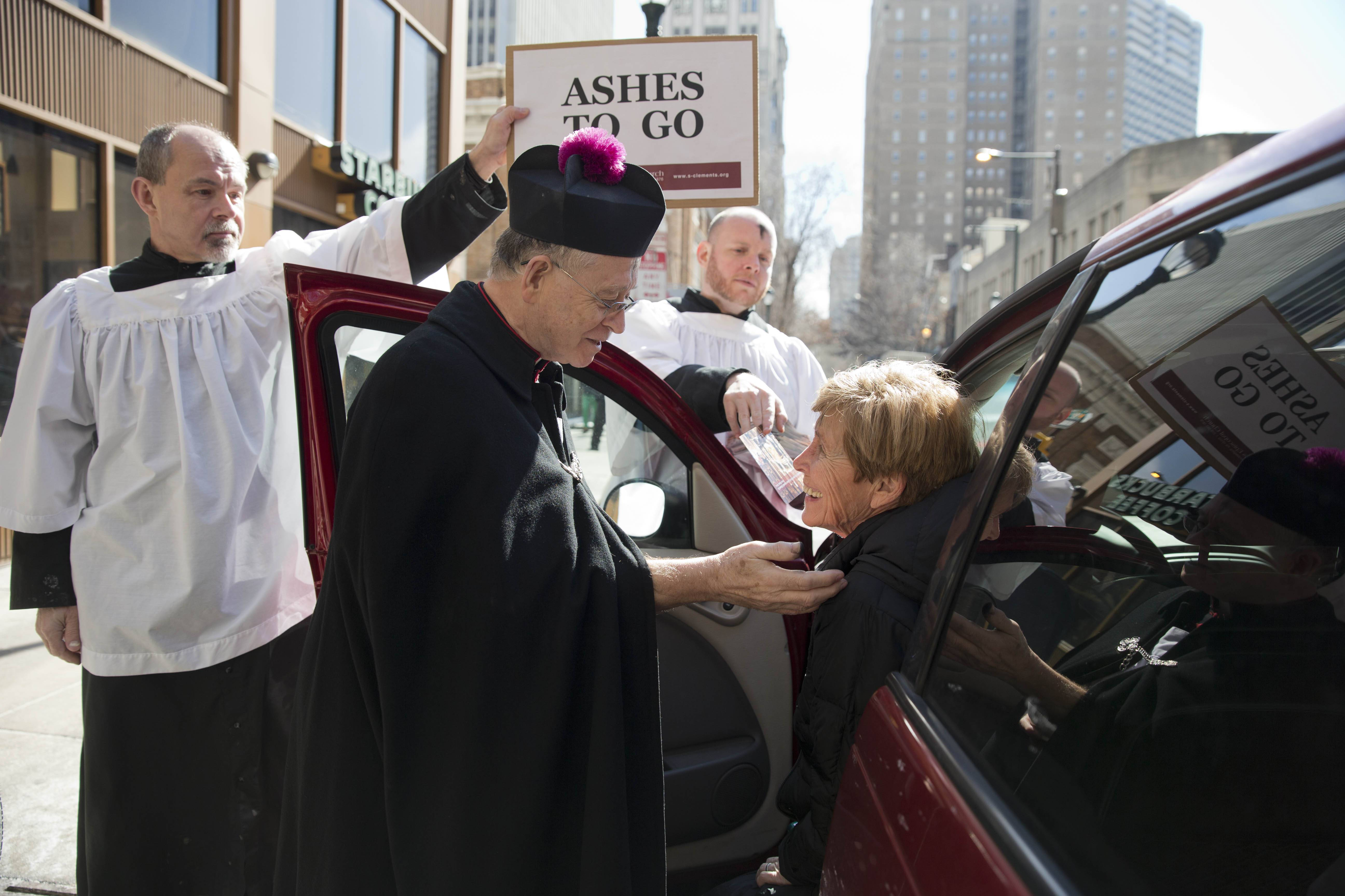 The Rev. Gordon Reid, center, with Saint Clement's Episcopal Church, accompanied by Curt Mangel, left, and Daniel Craig, center right, places ash on a worshiper's forehead on Ash Wednesday at the corner of Chestnut and 19th Streets in Philadelphia.