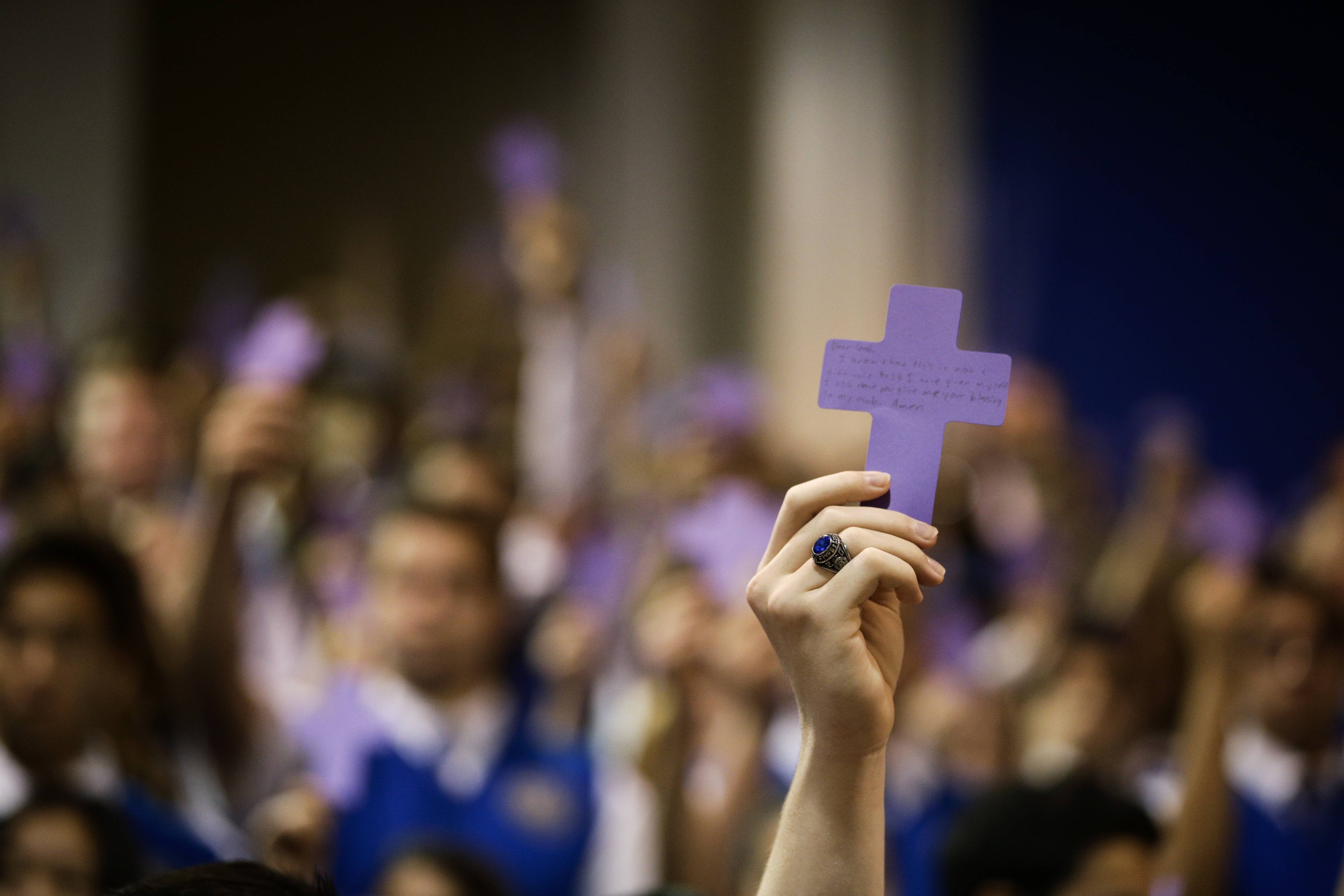Students hold up paper crosses during an Ash Wednesday Mass at Santa Margarita Catholic High School on Wednesday, March 5, 2014, in Rancho Santa Margarita, Calif.