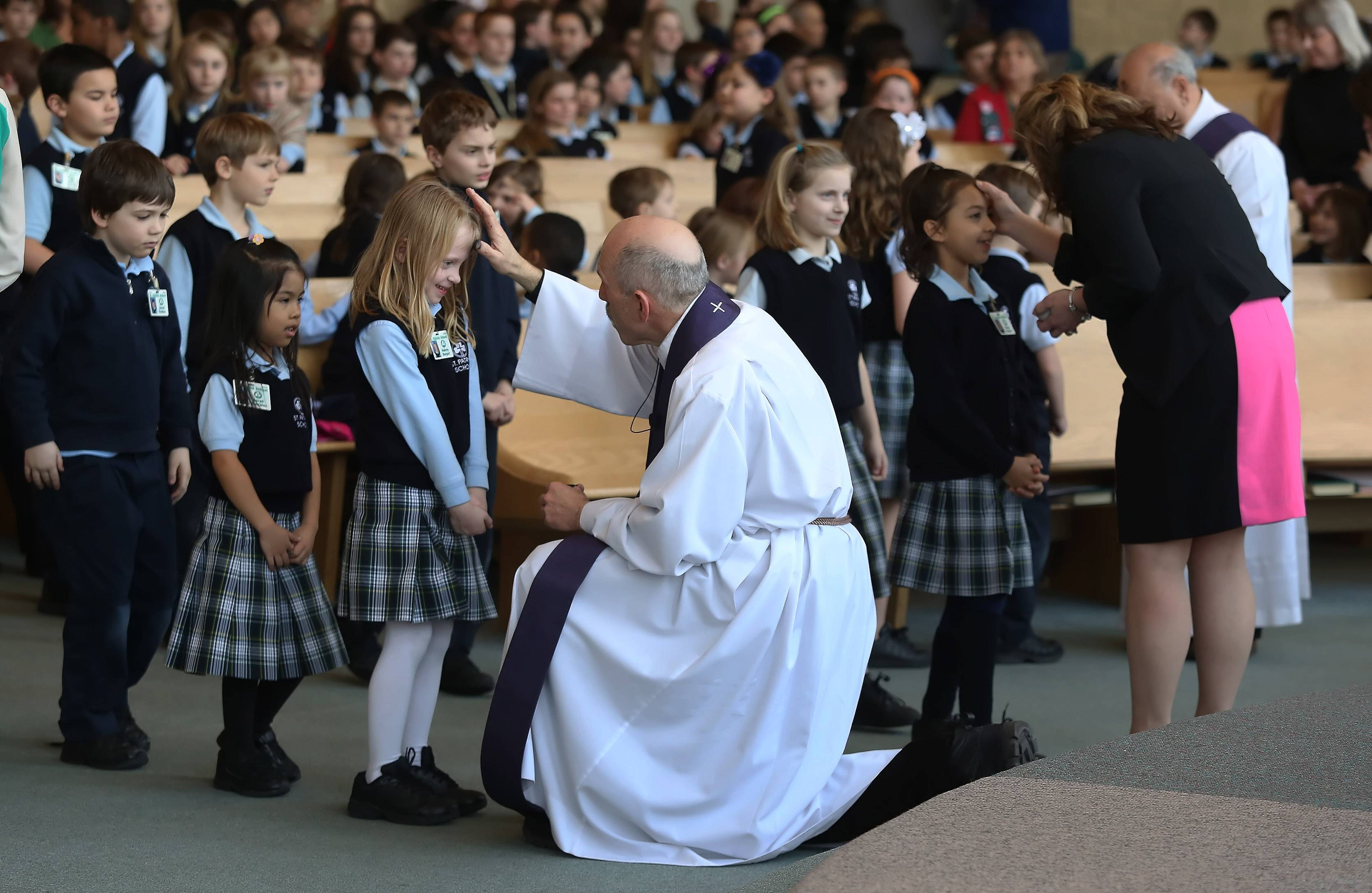Father Fred Pesek places ashes on the forehead of St. Patrick School kindergartners at St. Patrick Catholic Church in Wadsworth.