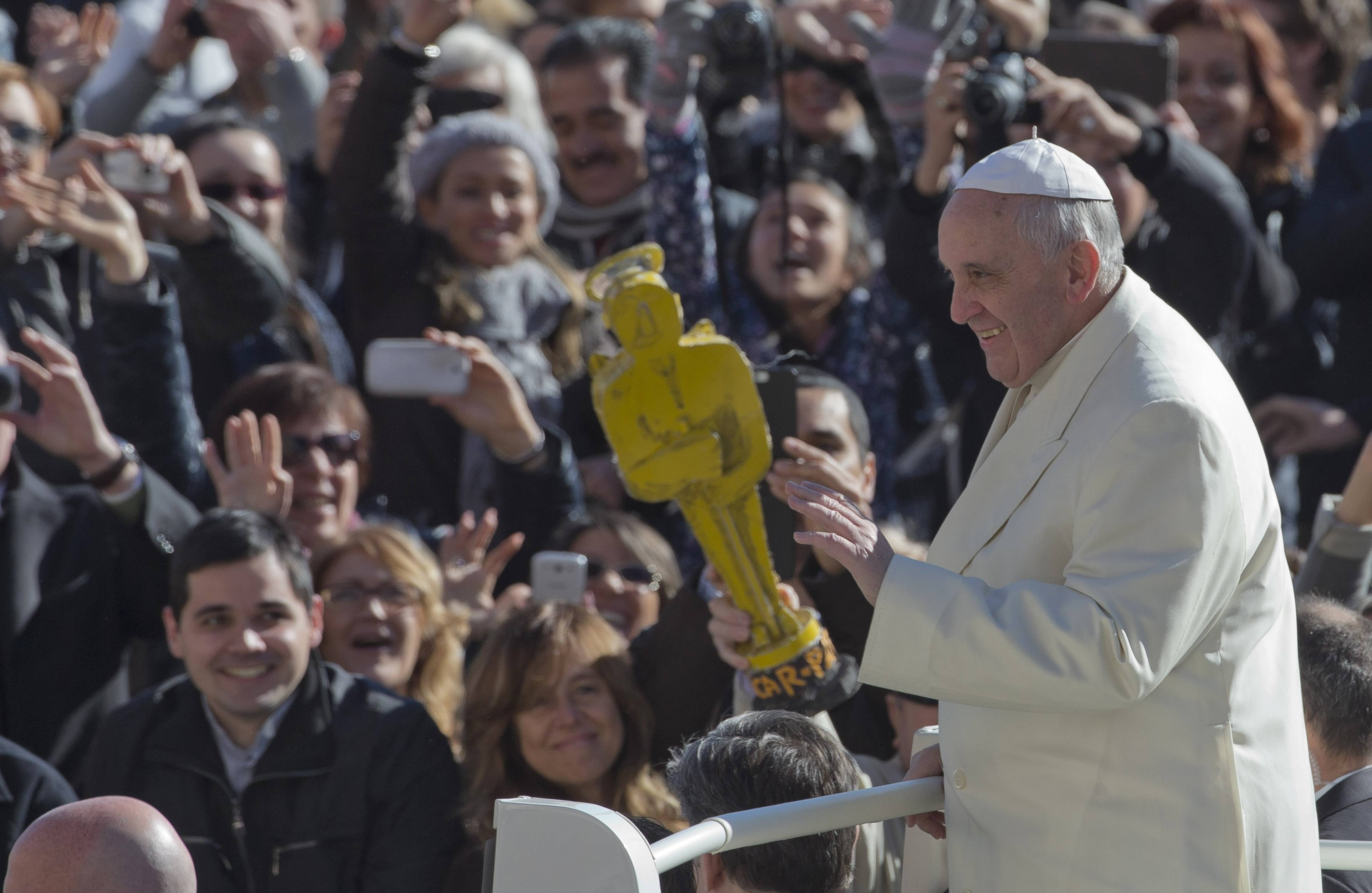 "A person holds a mock Oscar statue as Pope Francis tours St. Peter's Square at the Vatican prior to the start of his weekly general audience. The pontiff says he finds the hype that is increasingly surrounding him ""offensive."""
