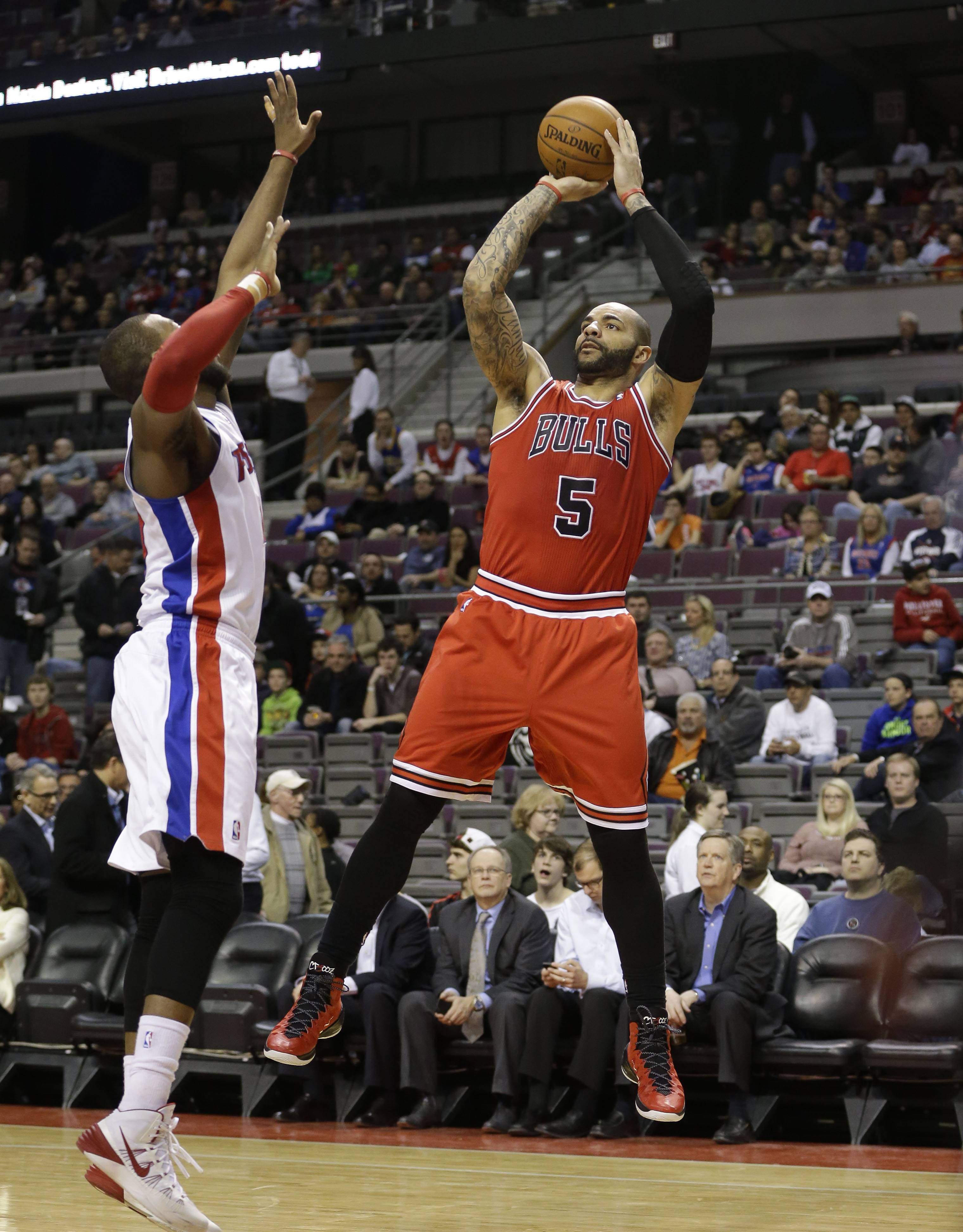 Chicago Bulls forward Carlos Boozer (5) shoots over Detroit Pistons forward Greg Monroe during the first half of an NBA basketball game in Auburn Hills, Mich., Wednesday, March 5, 2014.