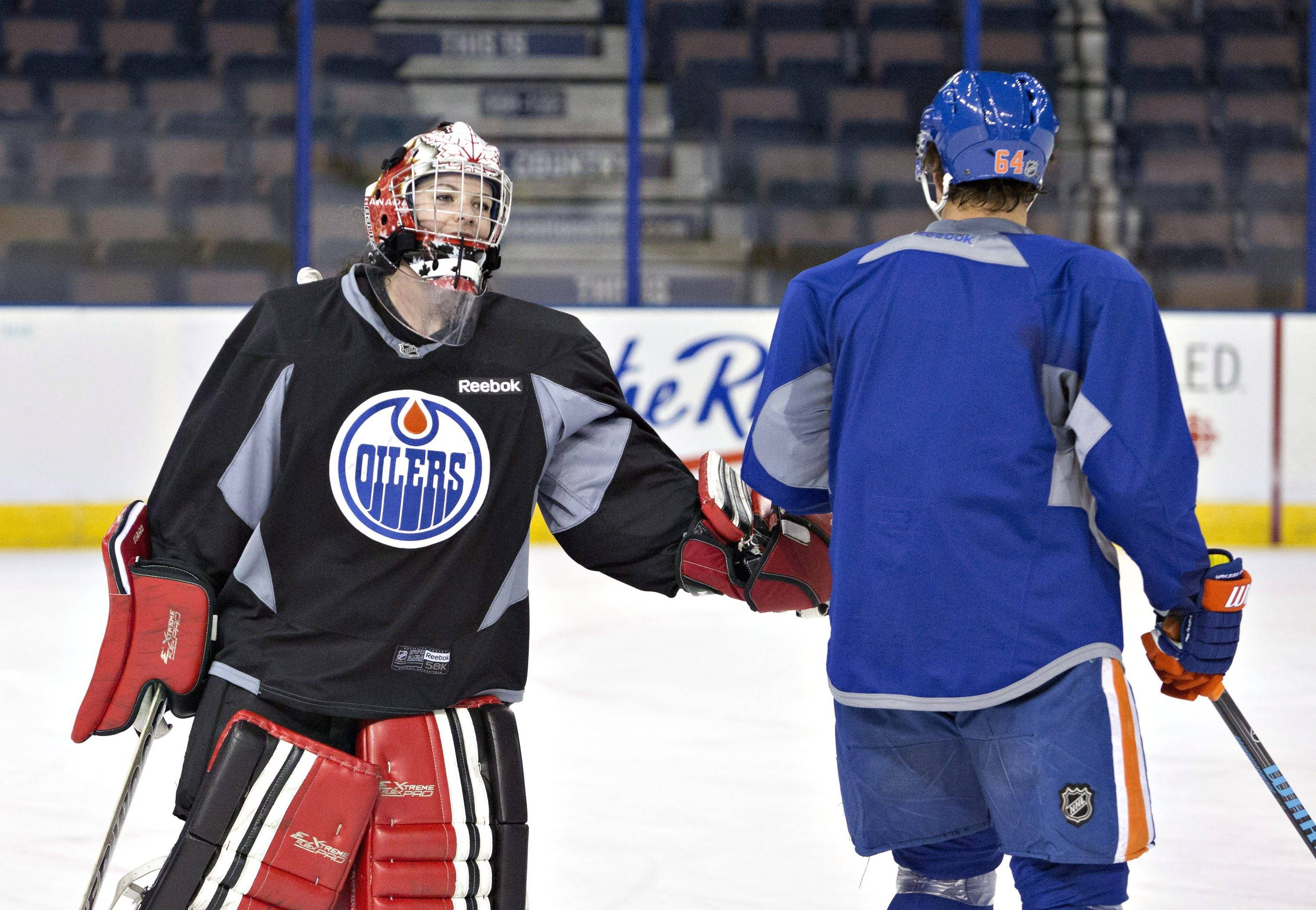Canadian Olympic women's team goalie Shannon Szabados gives a low-five to Nail Yakupov during practice with the Edmonton Oilers NHL hockey team in Edmonton, Alberta, Wednesday, March 5, 2014.