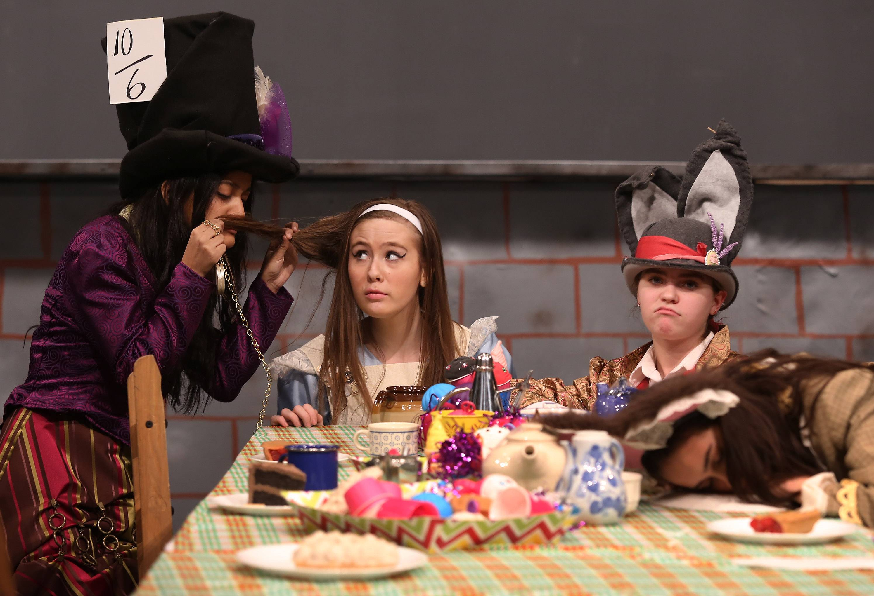 "Lake Zurich Middle School South students Ria Talukder (Madhatter), left, Morgan Coirier (Alice), Emma Belew (the March Hare) and Lindsey Lang (the Door Mouse) perform a scene during Thursday's dress rehearsal for ""Alice in Wonderland."""