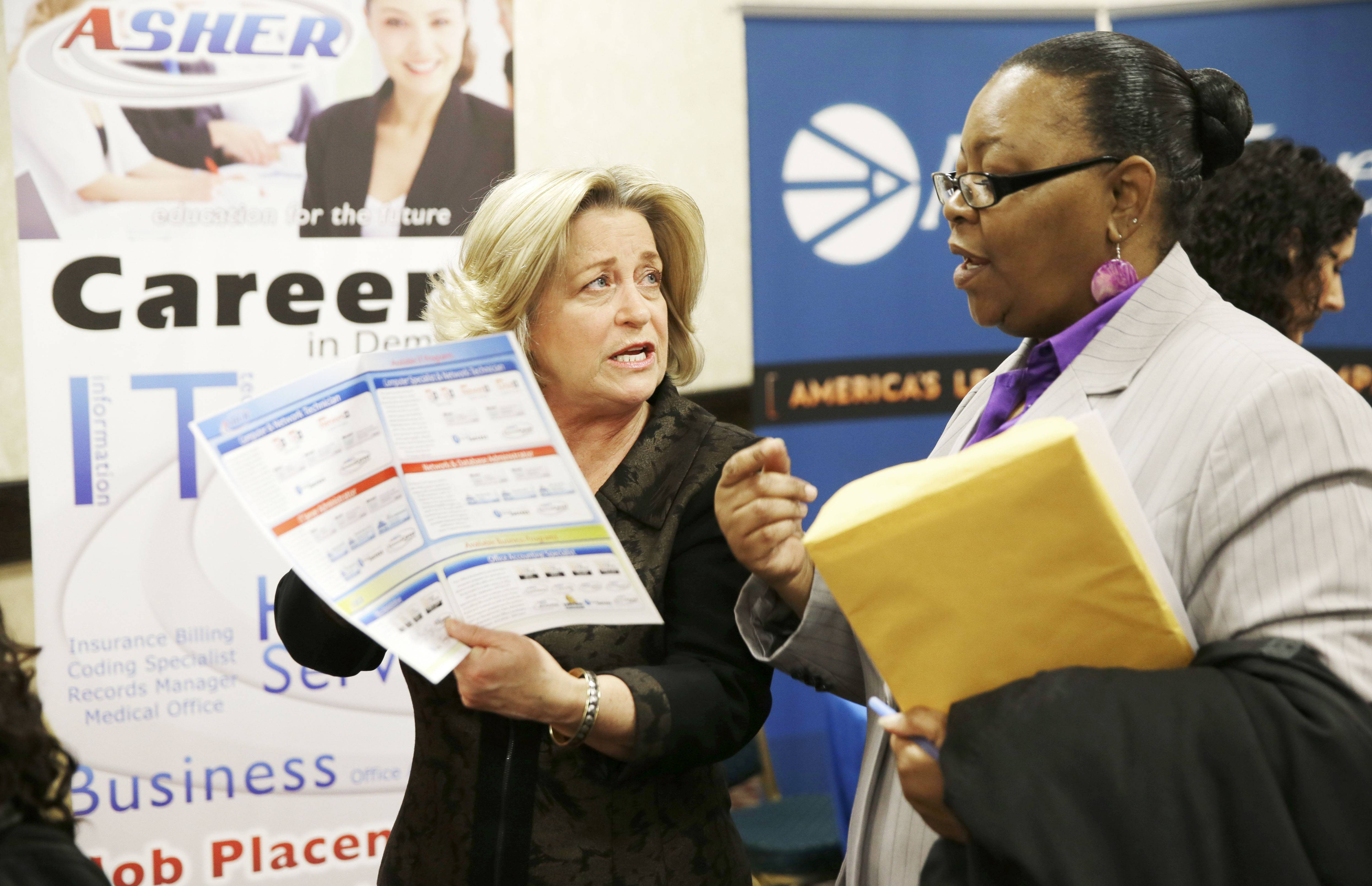 Recruiter Valera Kulow, left, speaks with job seeker Monic Spencer during a career fair in Dallas.