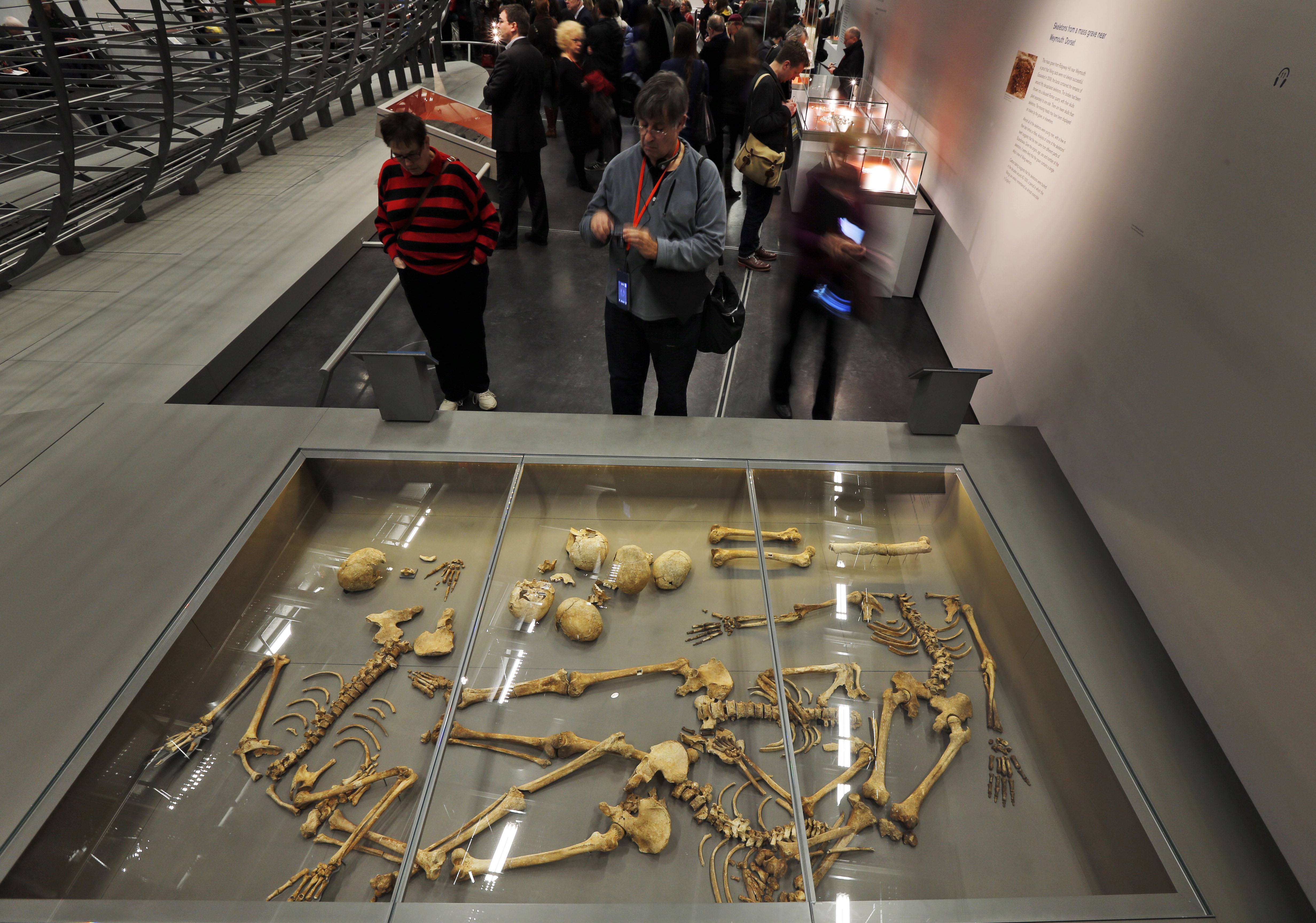 "Visitors look at some of the 50 headless skeletal remains of young men found in a mass grave on England's south coast, apparently a Viking raiding party that failed, at a new exhibition entitled ""Vikings: Life and Legend"" at the British Museum in London."