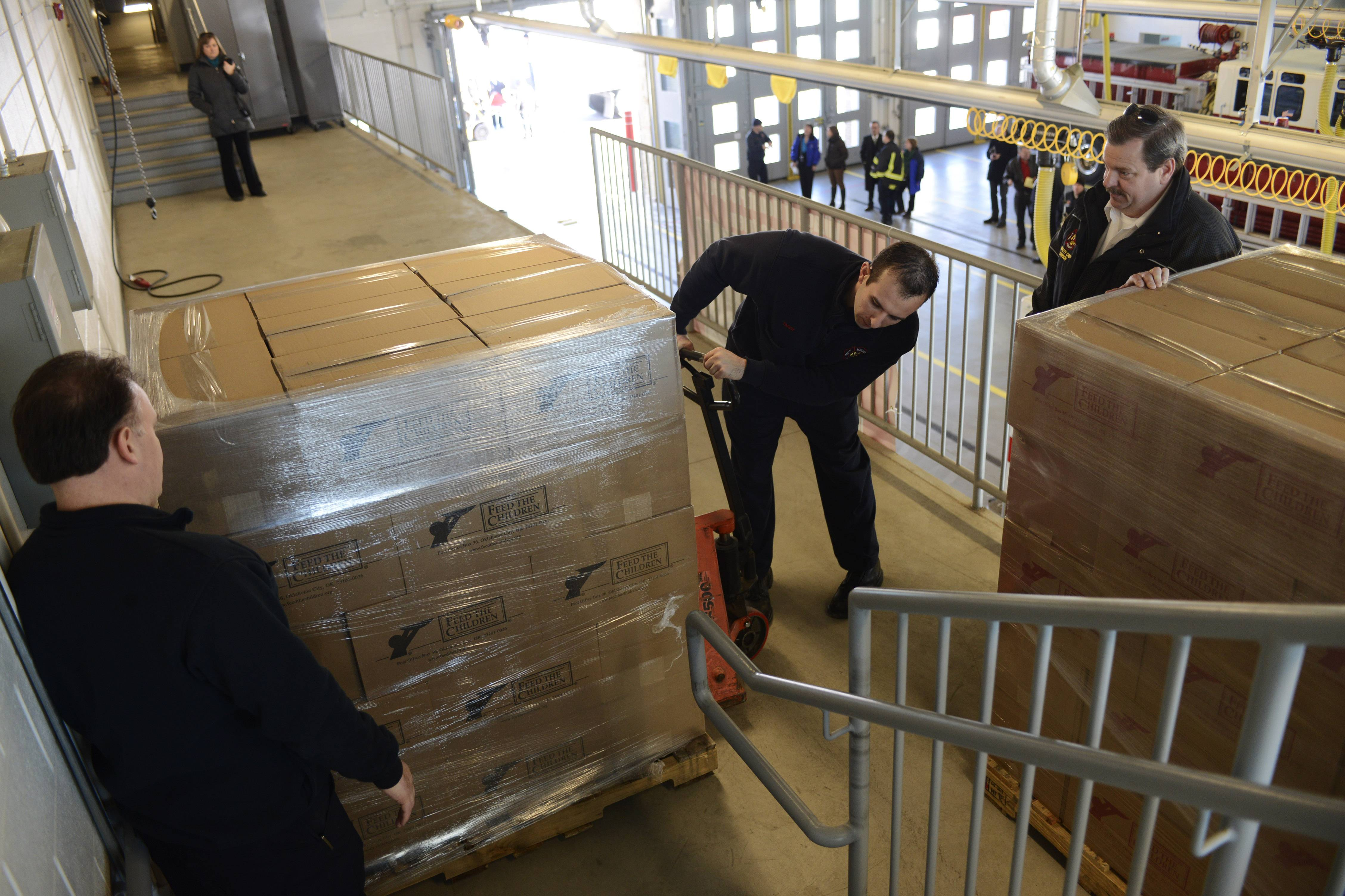 Firefighter/paramedics Anthony Minarcik, left, and Matt Tackoy unload a pallet with the assistance of Deputy Fire Chief Henry Dawson, right, as Feed the Children delivered a trailer full of food to Mount Prospect Fire Station 14 on Kensington Road.