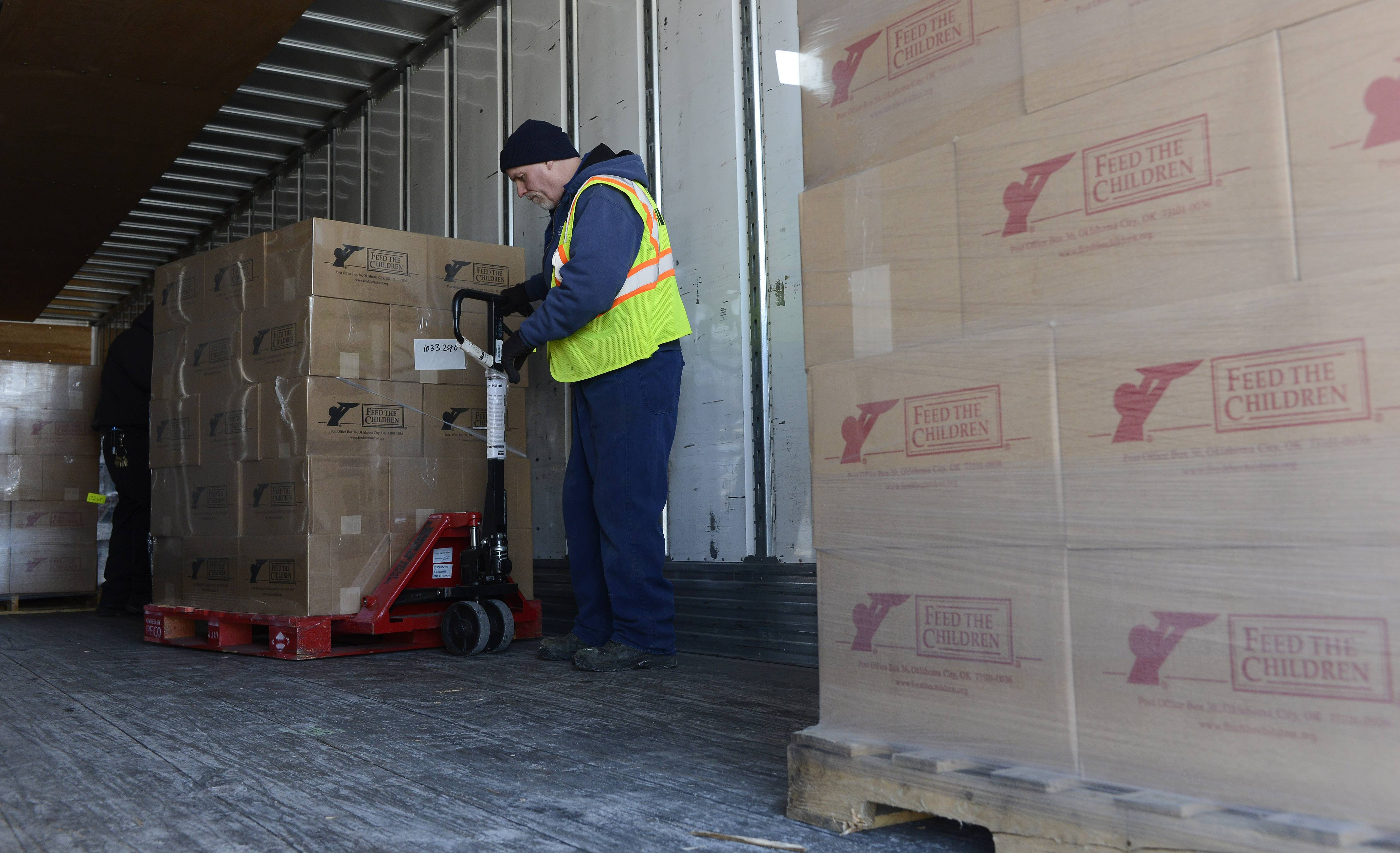 Con Erskine of Mount Prospect Public Works moves pallets of food and other items donated Thursday by Feed the Children at Mount Prospect Fire Station 14 on Kensington Road. The donation will benefit more than 400 struggling families in Mount Prospect.