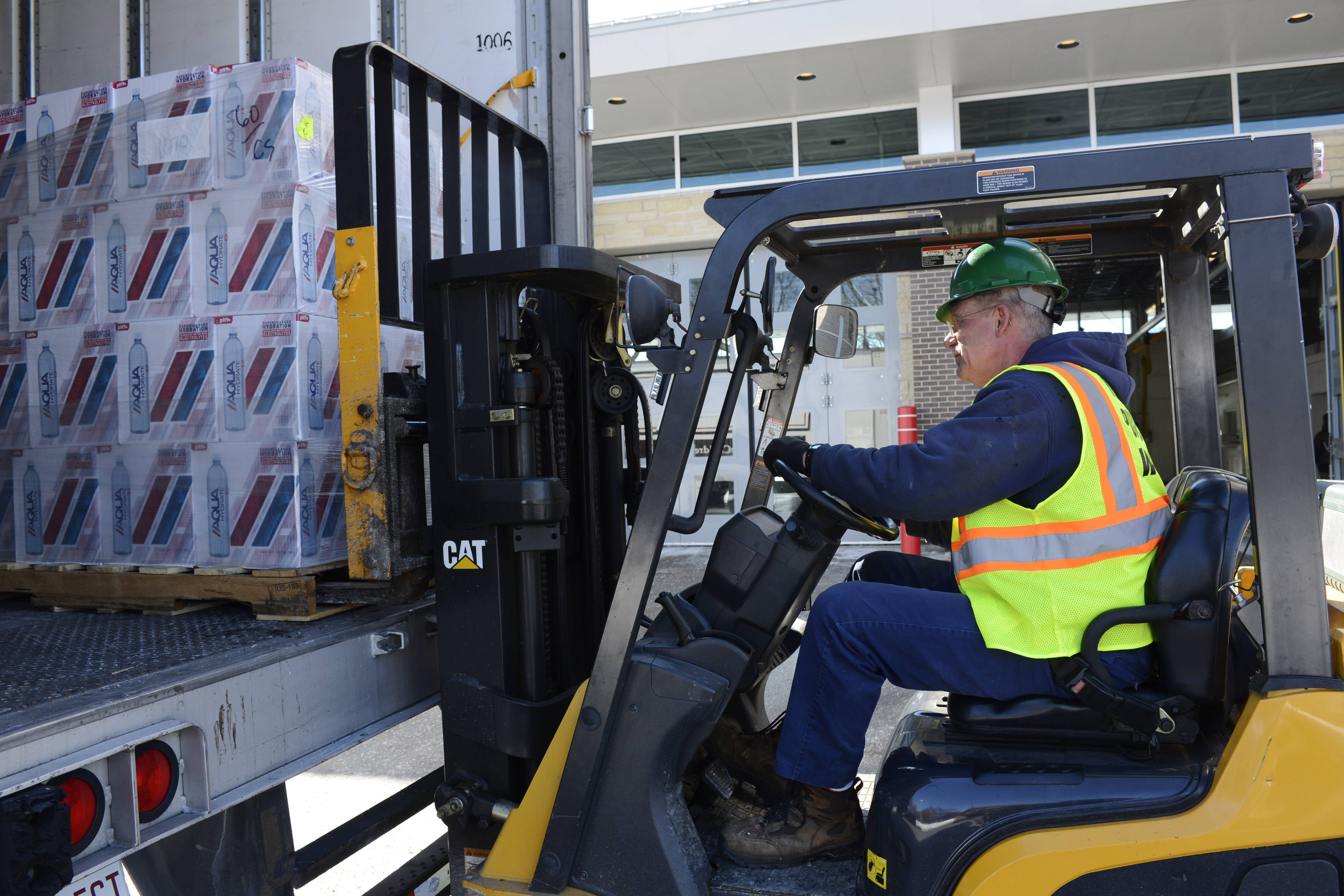 Steve Balogh of Mount Prospect Public Works lifts a pallet of bottled water donated Thursday by Feed the Children delivers at Mount Prospect Fire Station 14 on Kensington Road. The donation will benefit more than 400 struggling families in Mount Prospect.