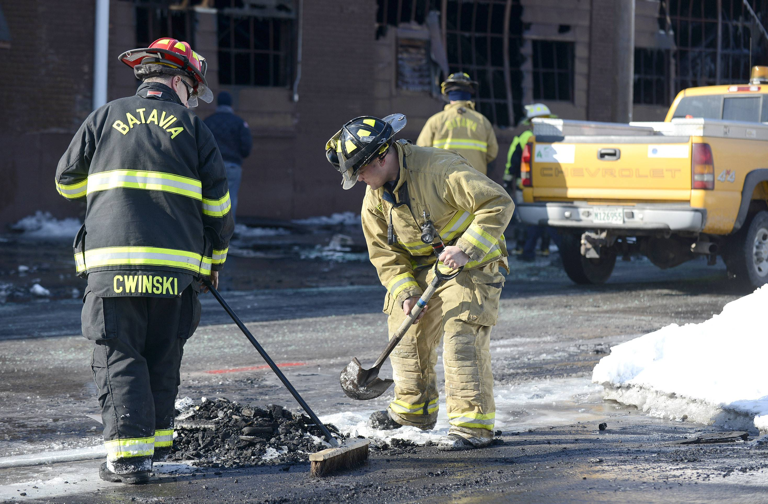 Batavia Fire Lt. Mark Cwinski and firefighter/paramedic Kit Miner clean up burned debris in front of Master Cast Thursday morning, as one engine from the department was still on hand from the fire the night before. Both firefighters worked at the site through the night.