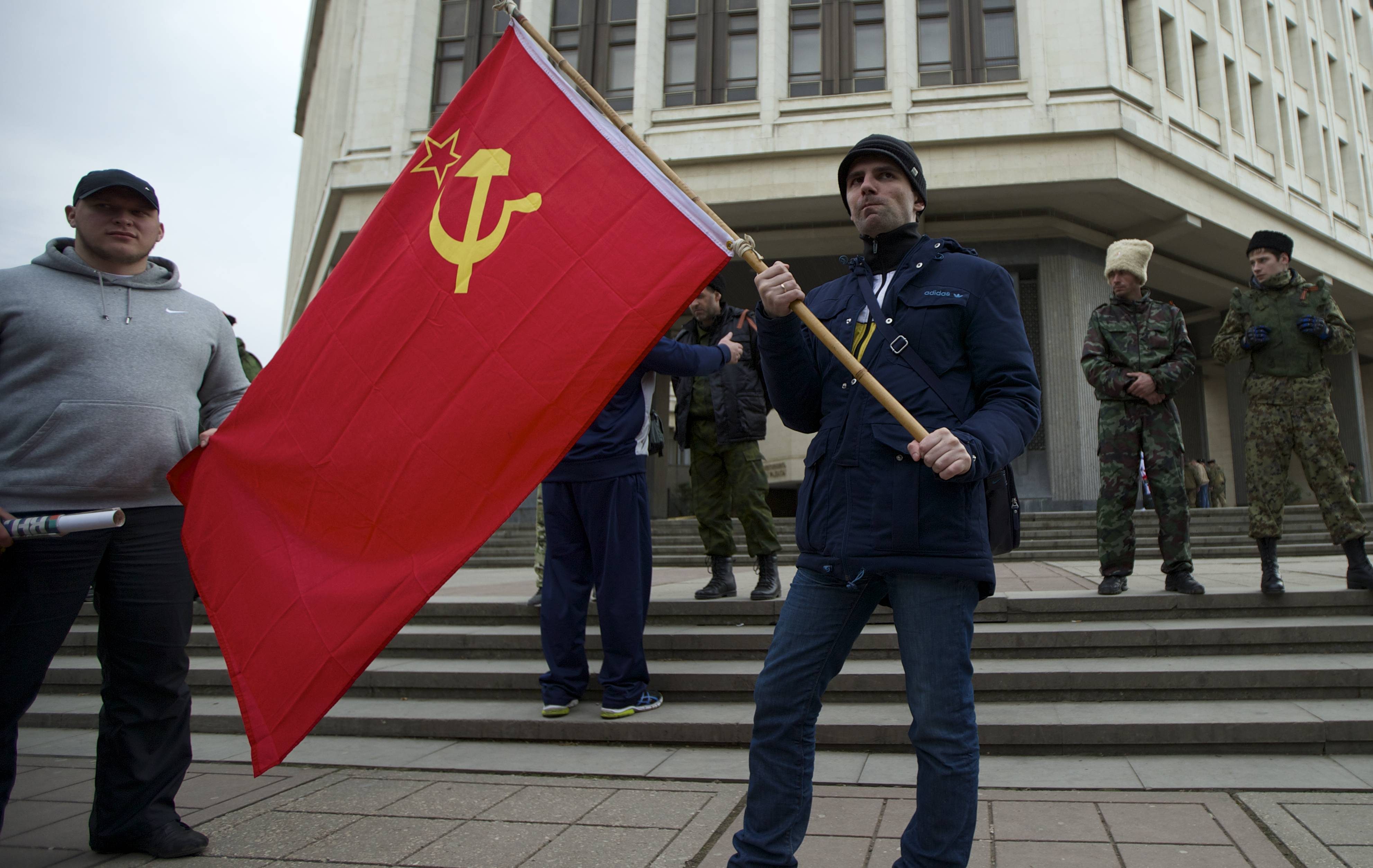 Local residents hold a Soviet flag as members of Cossack militia guard the local parliament building in Simferopol, Ukraine, Thursday. Lawmakers in Crimea declared their intention to split from Ukraine and join Russia instead, and scheduled a referendum in 10 days for voters to decide the fate of the disputed peninsula.