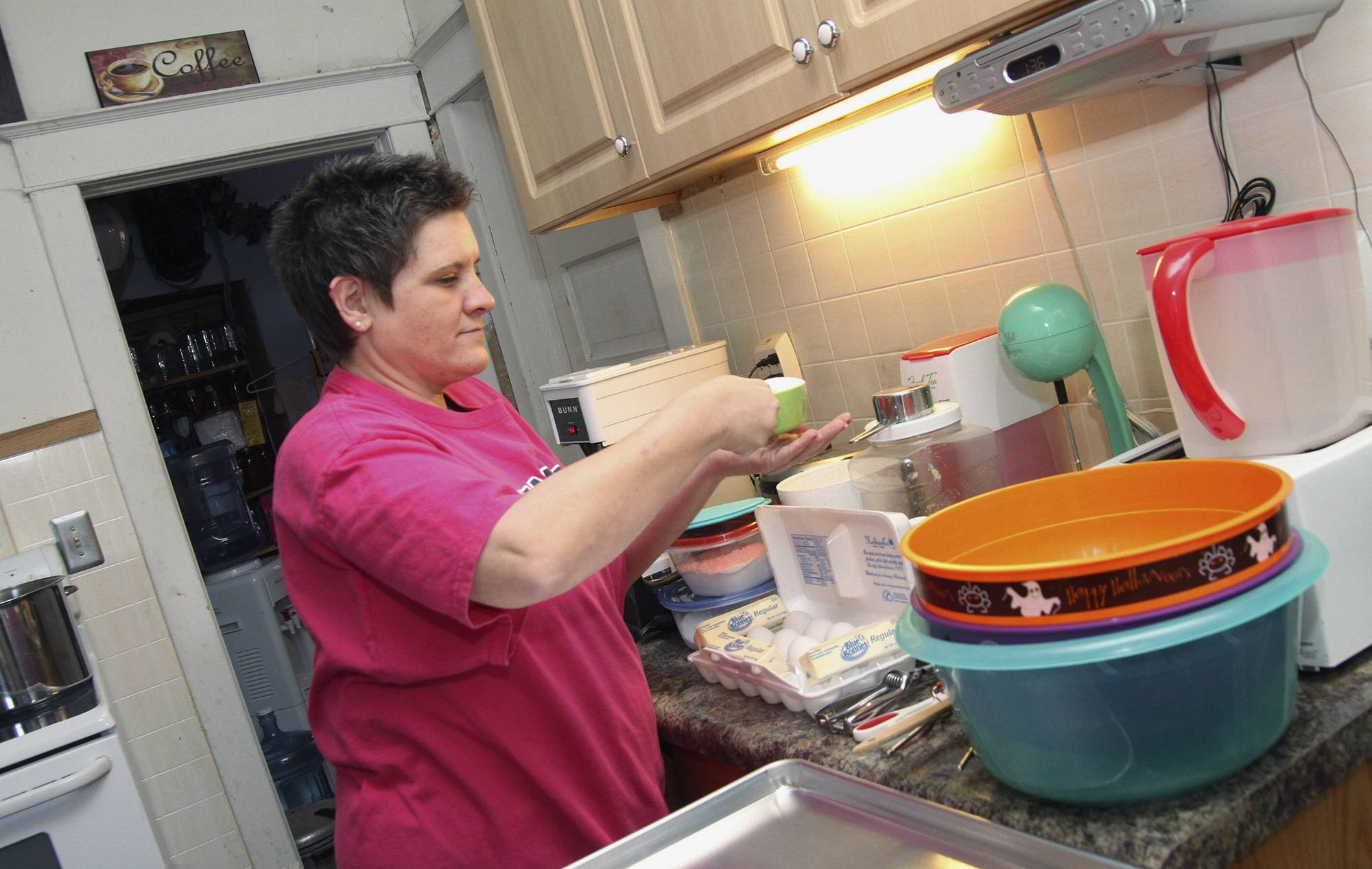 Melissa Dunning measures ingredients for a batch of cookies at her home in Kinsman.