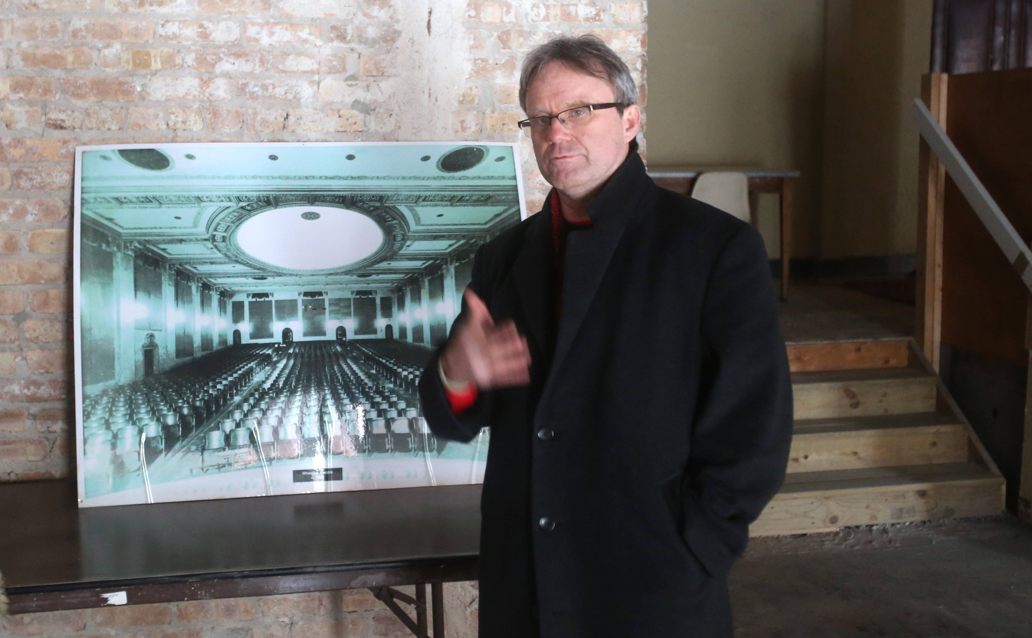Flanked by a photo taken in 1950 of the Wheaton Grand Theater, Rick Erickson discusses plans to renovate it.