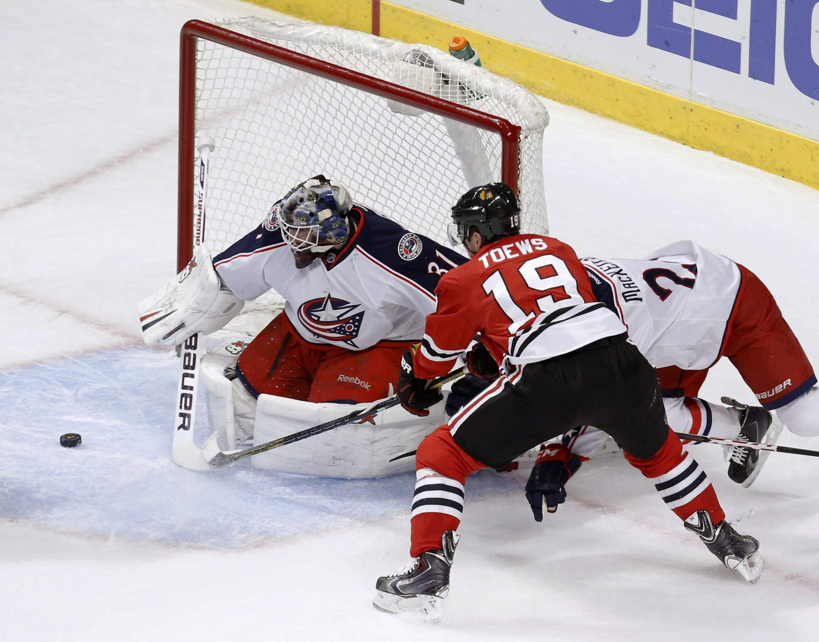 Columbus Blue Jackets goalie Curtis McElhinney makes Blackhawks center Jonathan Toews shoot wide of the net as Derek MacKenzie also defends during the second period Thursday in Chicago.