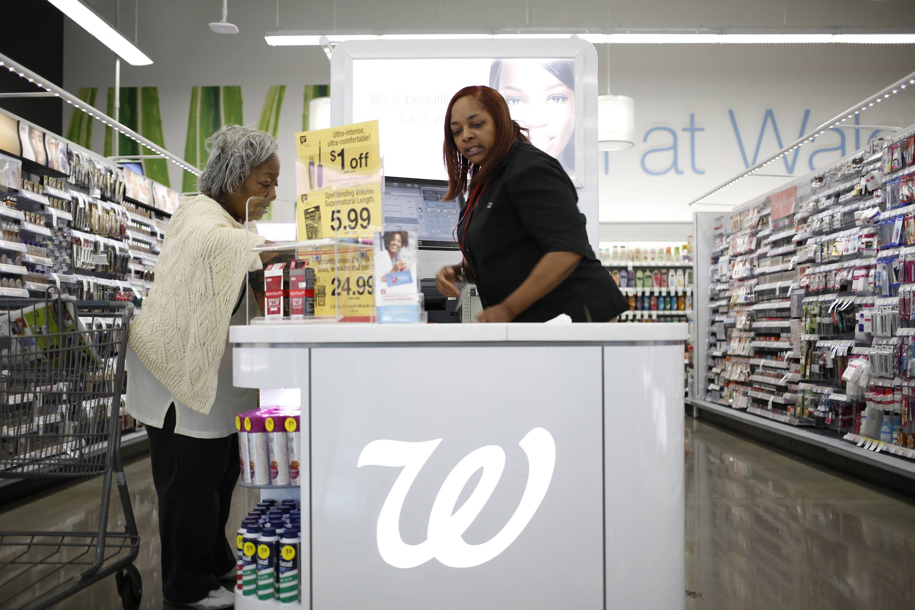 Customer Anna Board, left, checks out in the cosmetics section of a Walgreen Co. store in Louisville, Kentucky.