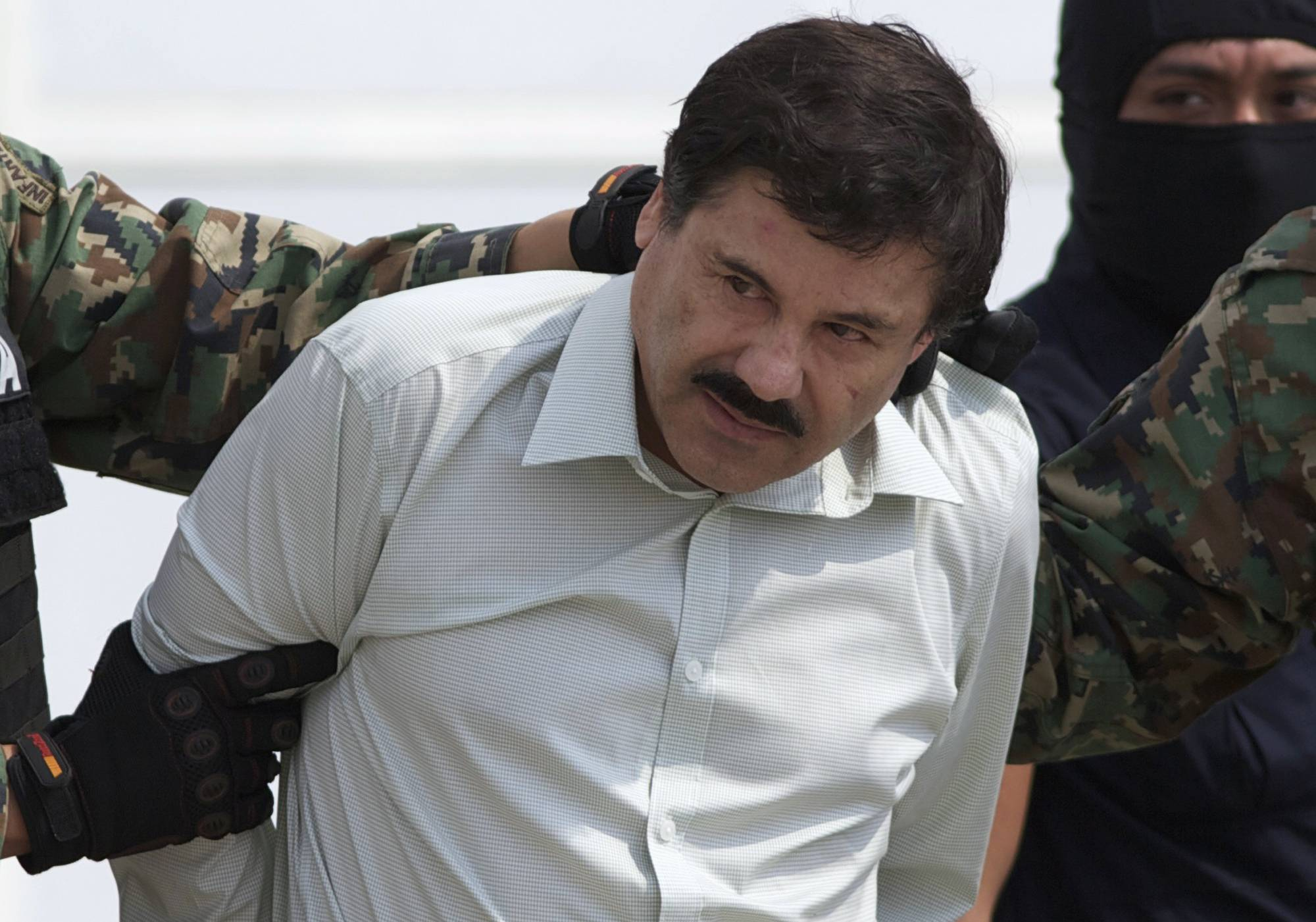 "Authorities escort Joaquin ""El Chapo"" Guzman, the head of Mexico's Sinaloa Cartel, to a helicopter in Mexico City after his capture in Mazatlan."