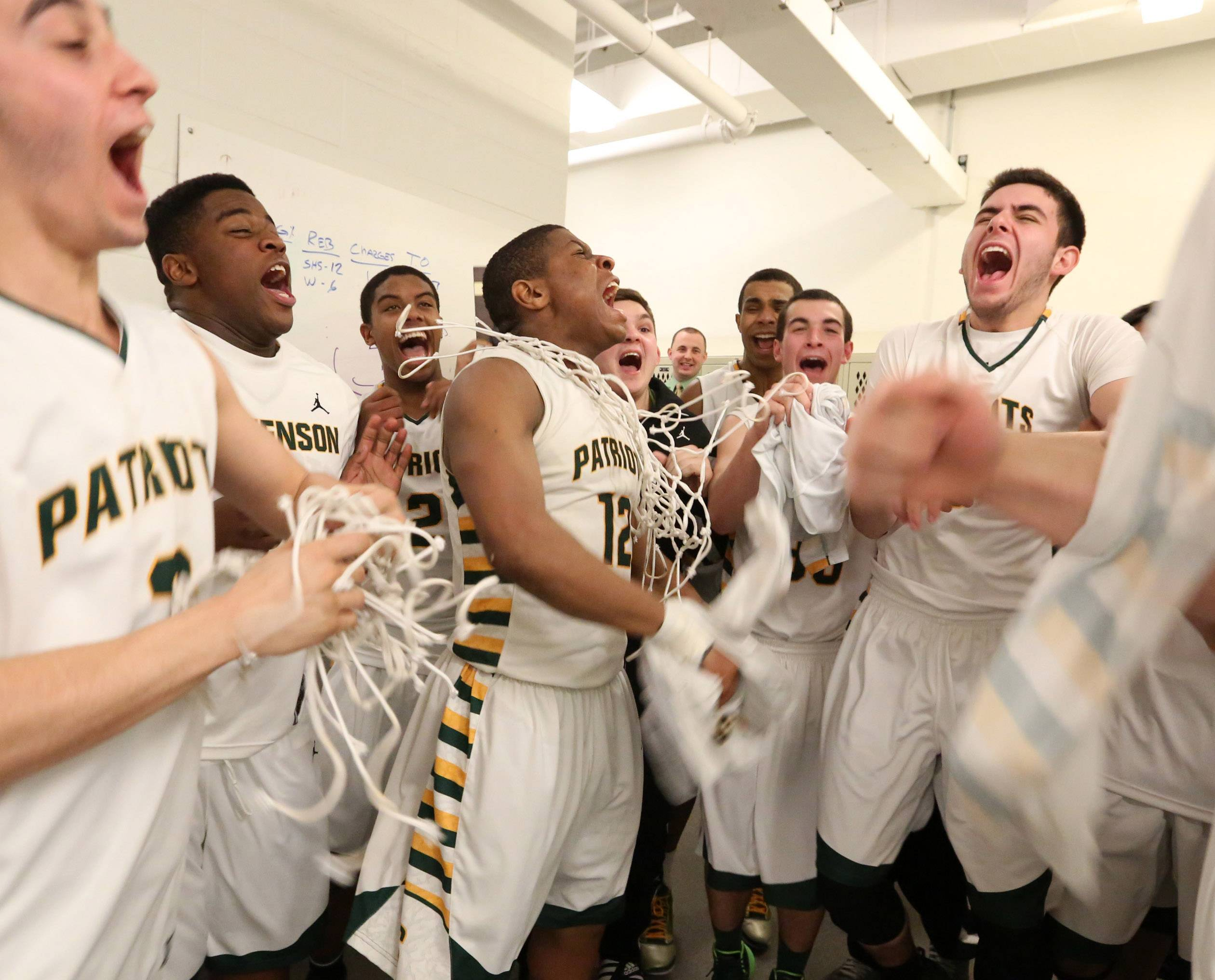 Stevenson celebrates in the locker room after topping Warren 79-59 in Class 4A regional final play at McHenry on Friday.